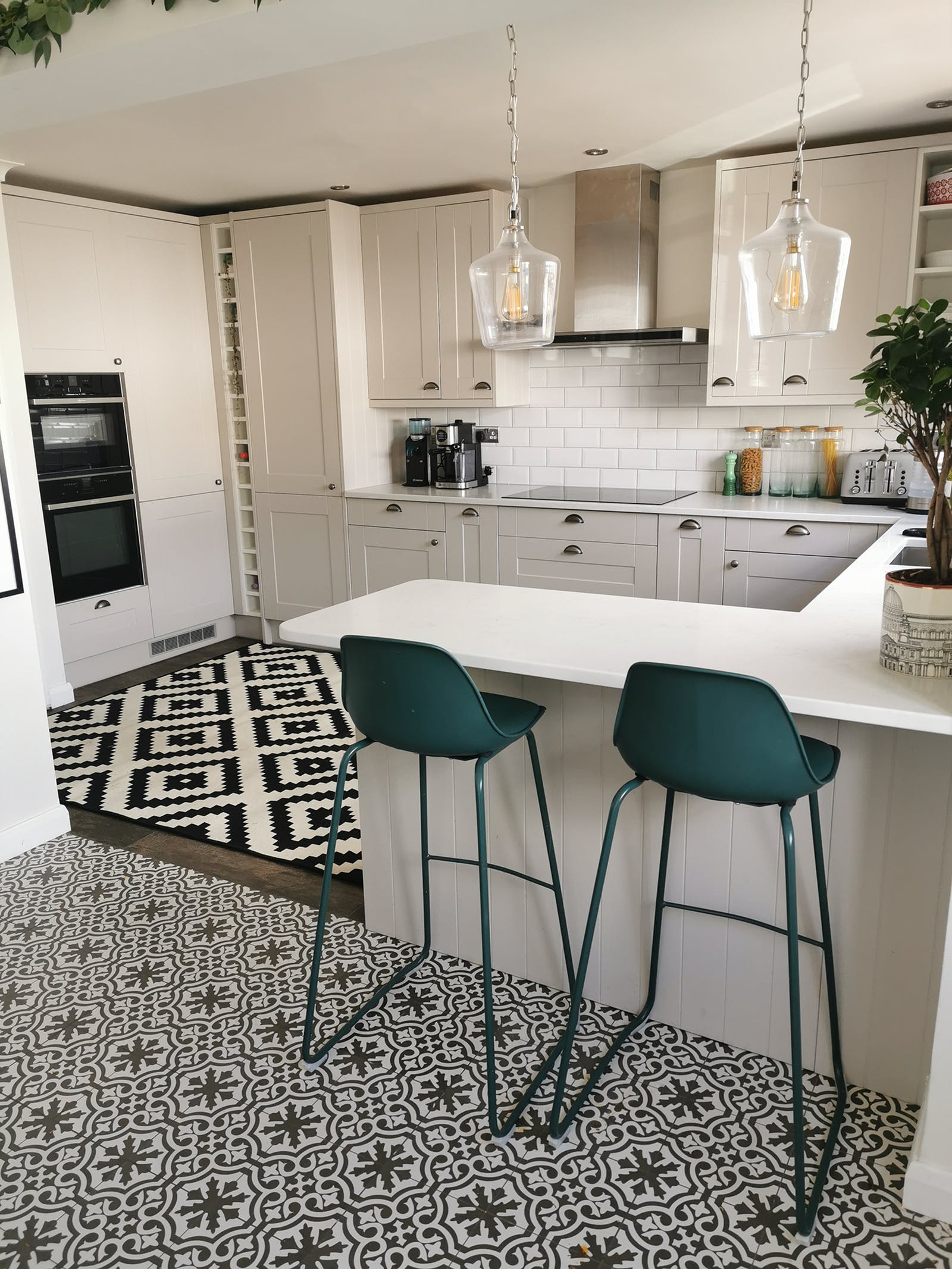 kitchen area with tall chairs and different patterned rugs