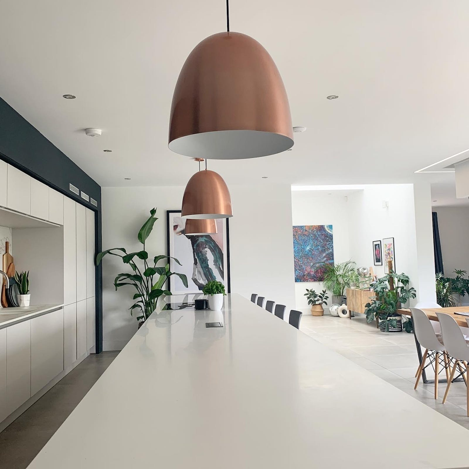Modern kitchen with long white island and large copper hanging lights