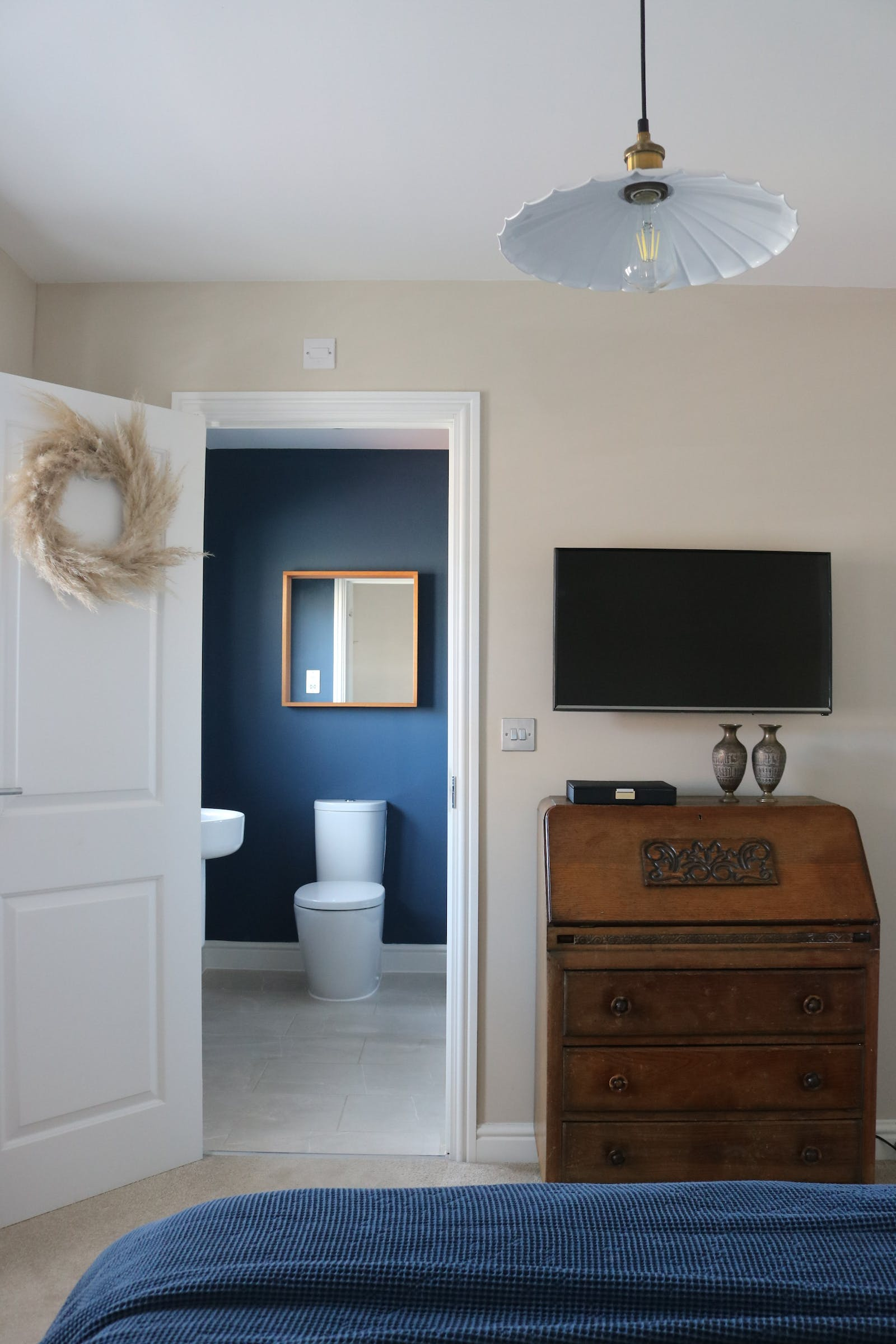 A view from a bedroom showing a blue-painted bathroom