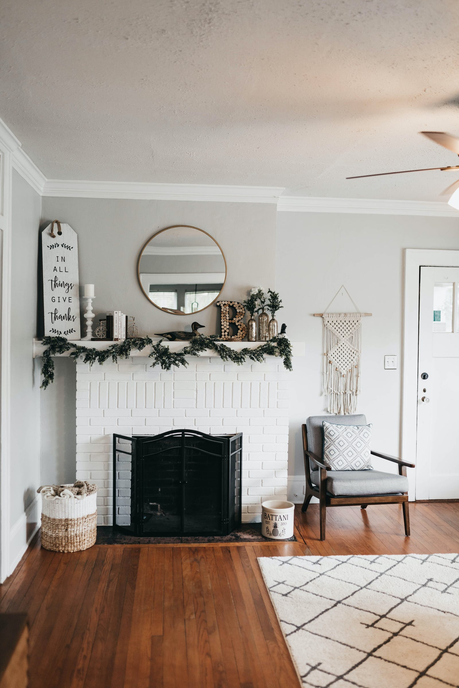 White room with circular mirror above fireplace