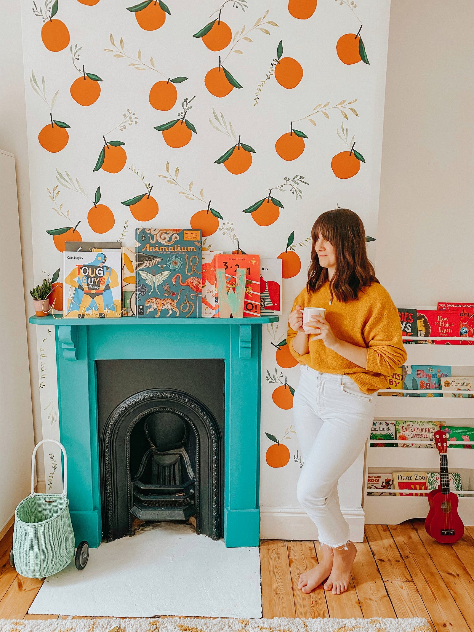 Brunette woman standing in front of turquoise fireplace with orange illustrated wallpaper