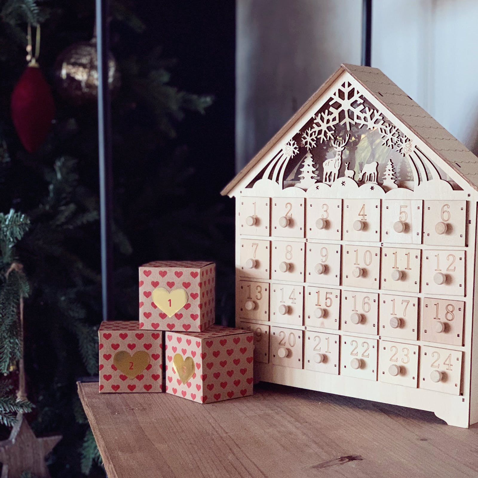Wooden advent calendar next to Christmas wrapped gifts