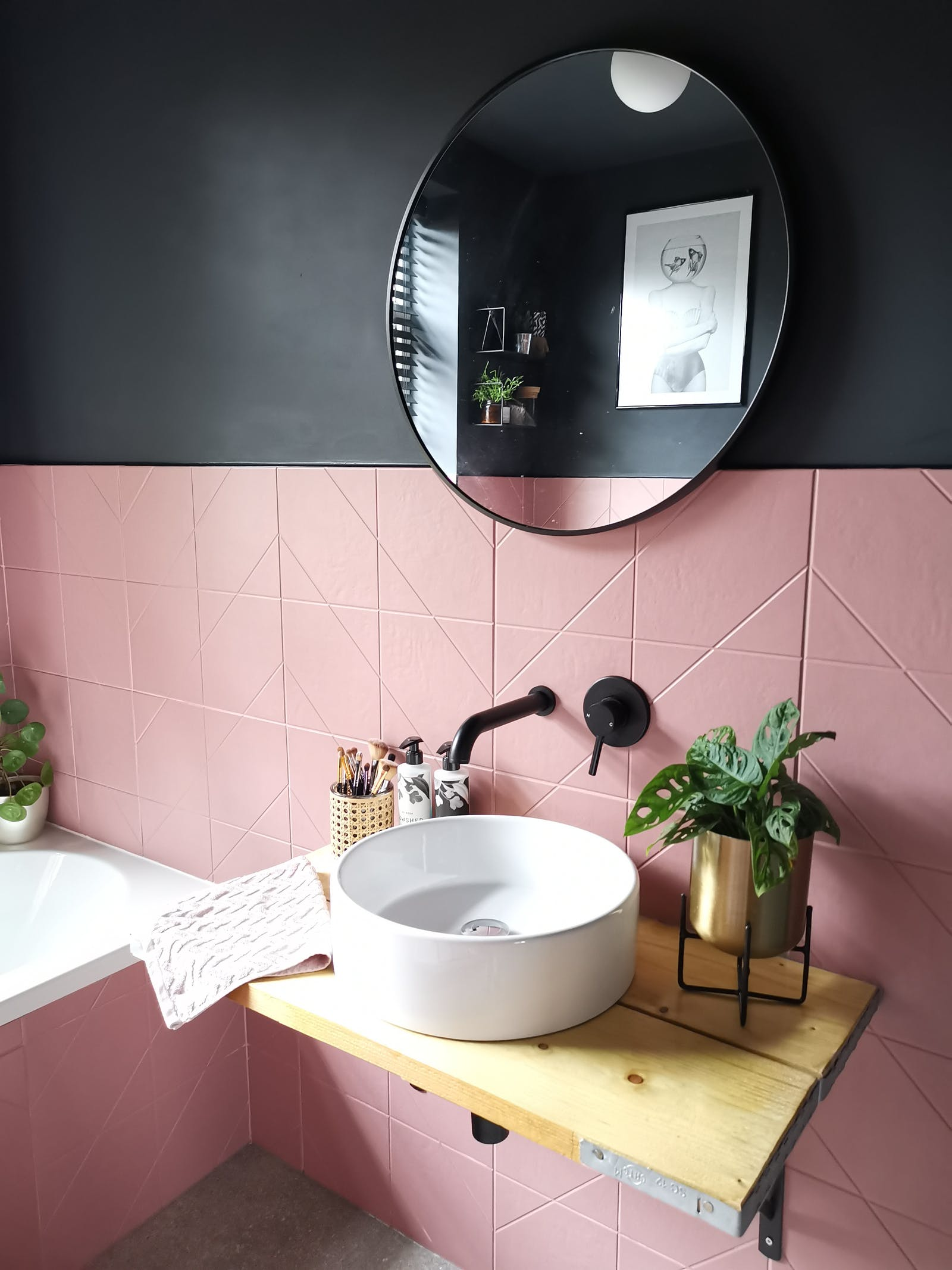 Bathroom painted in black with pink tiles and a wooden sink