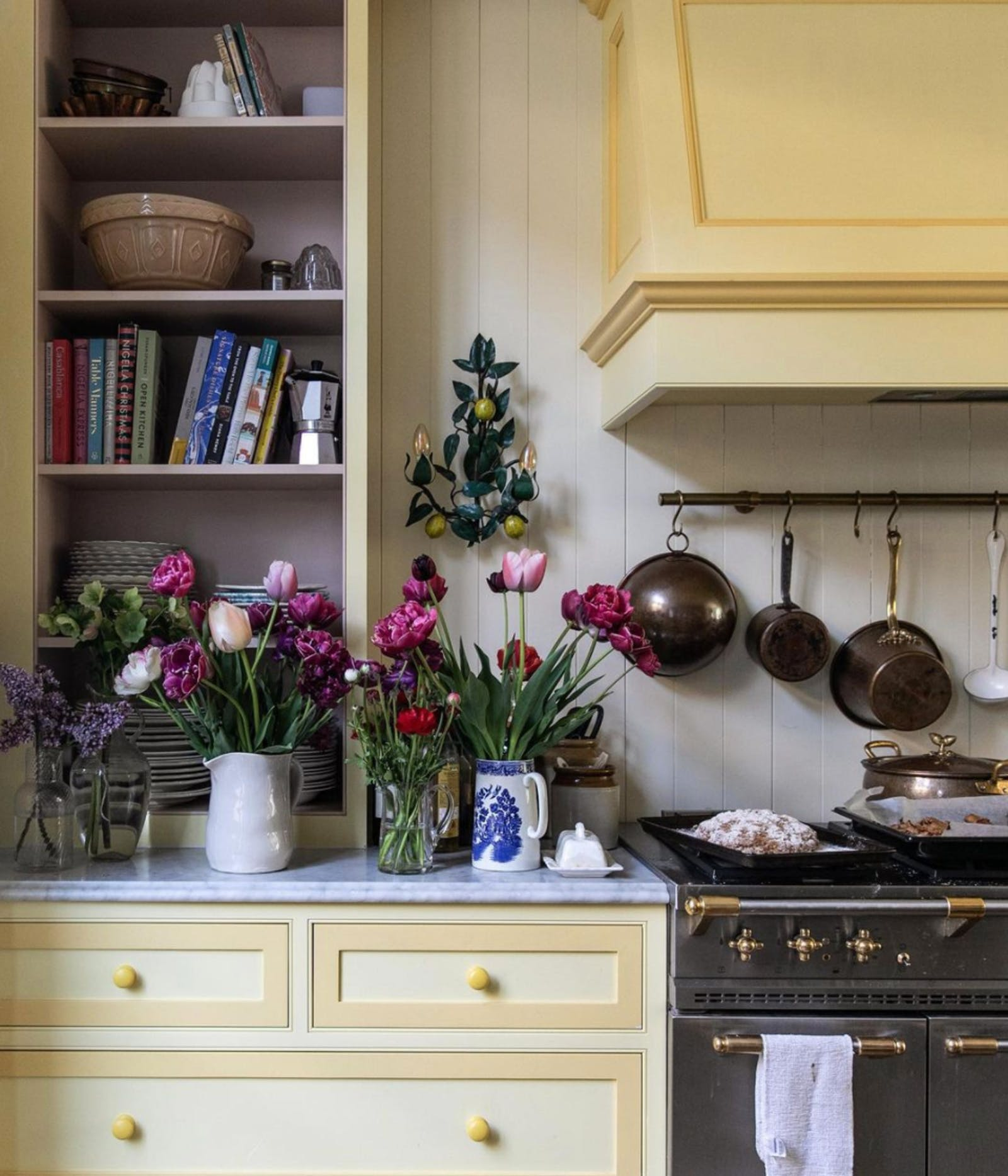 Kitchen with yellow cabinets and pink flowers