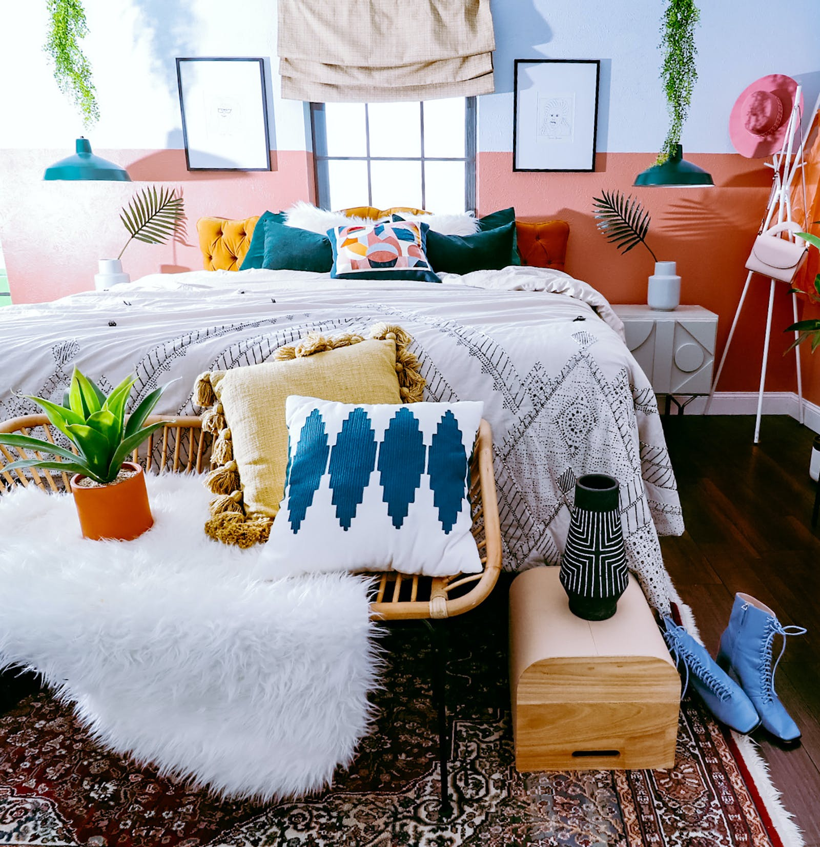 Image of bedroom with colour block wall, colourful pillows and plants