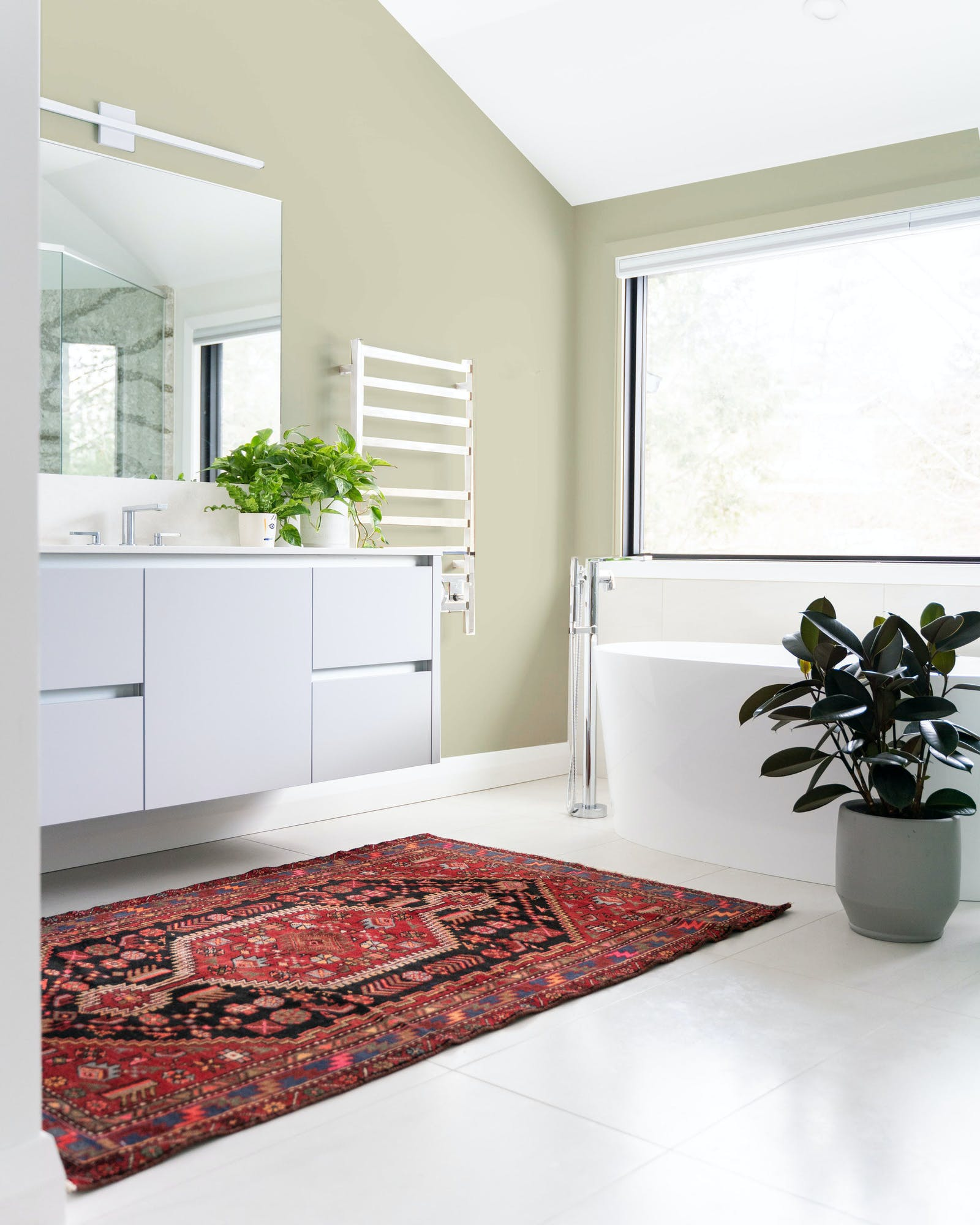 A clear white bathroom with red Persian rug and walls painted in Lick Greige 02