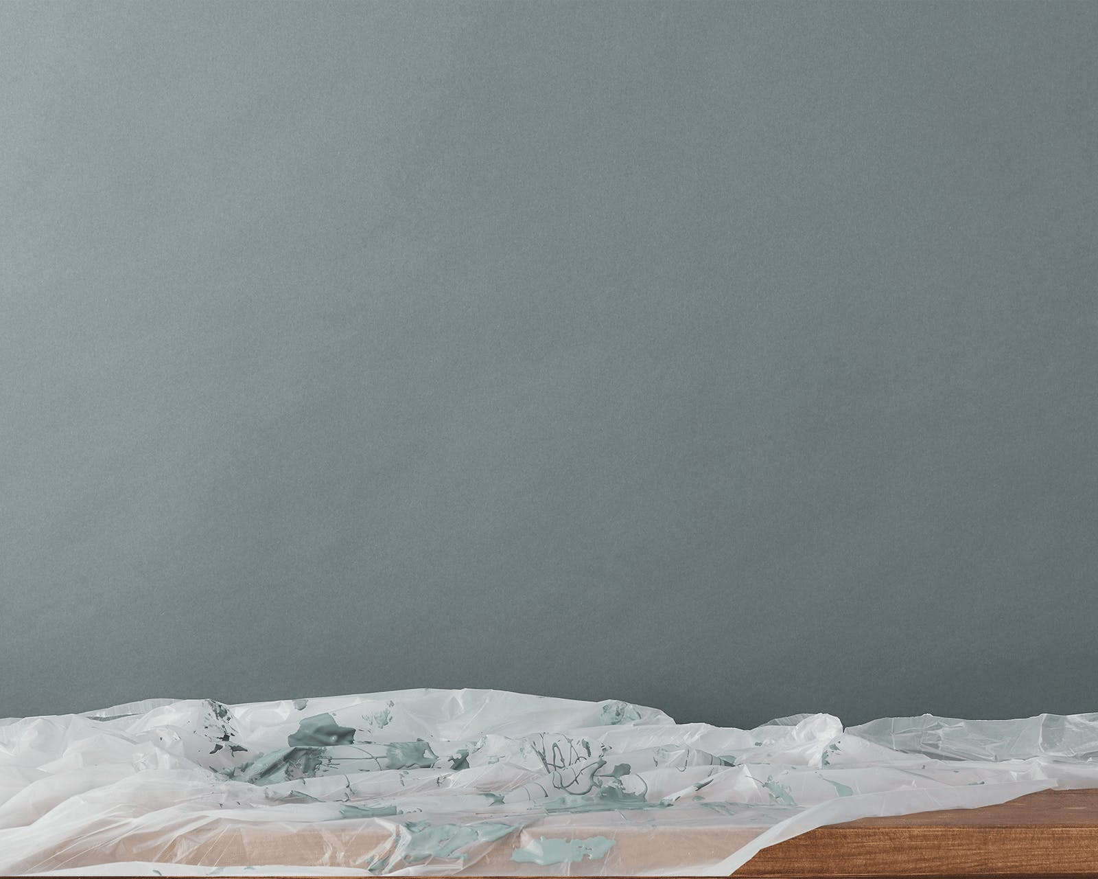 Image of a paint splattered bio dust sheet, protecting the floor from the freshly painted grey wall