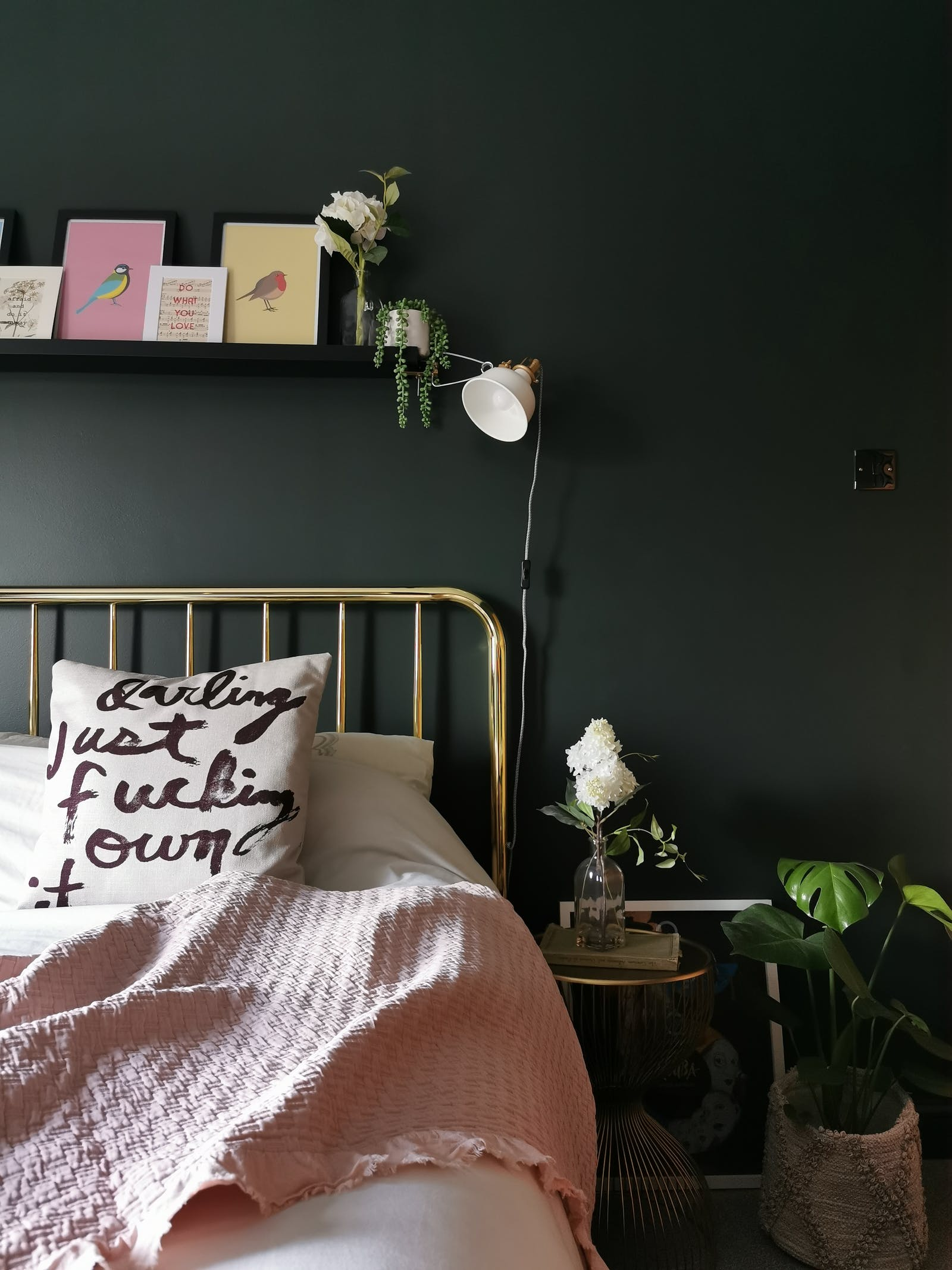 Bedroom in dark green with plants and wall decoration