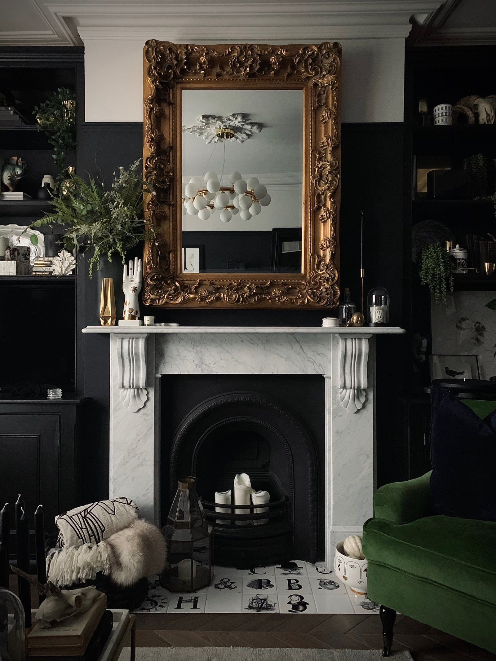Fireplace with a big vintage mirror reflecting on the lamps on the ceiling