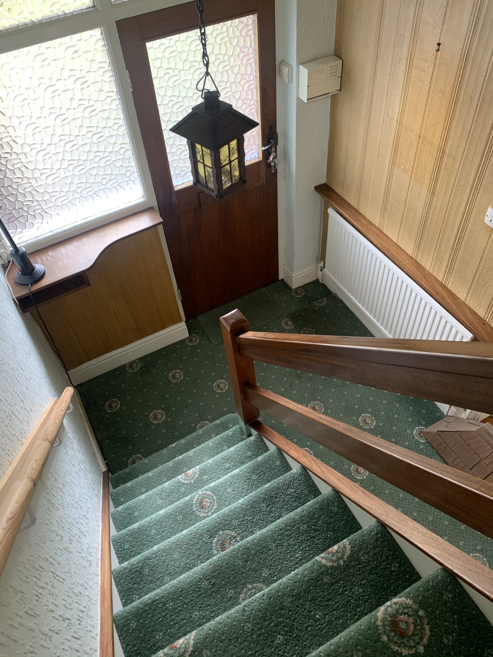 Image of dated green carpet running down stairs.