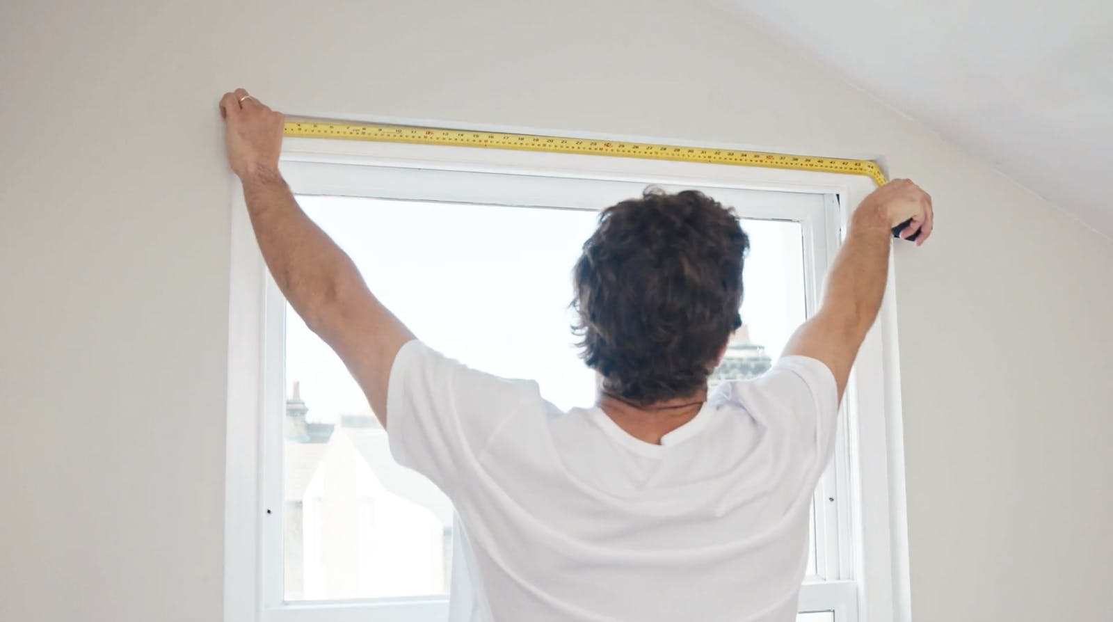 Man holding metal measuring tape to measure the recess of a window