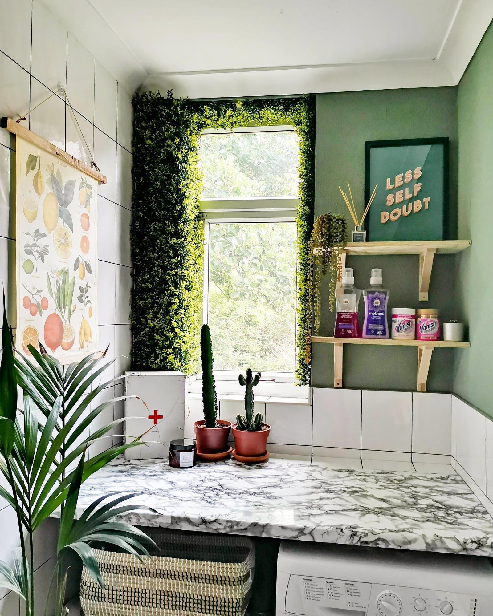 Laundry room painted in light green with a marble top and faux greenery window feature