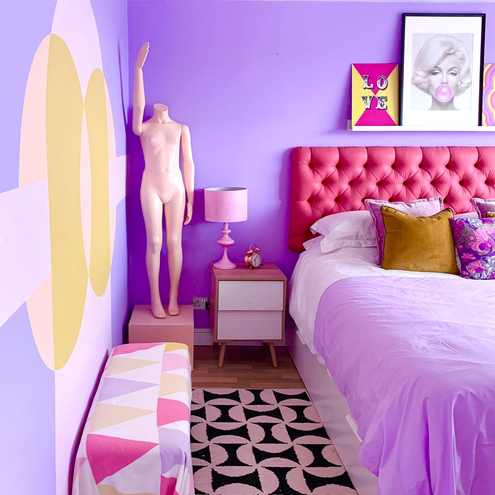 Bed wit pink headboard, purple bedding and purple walls