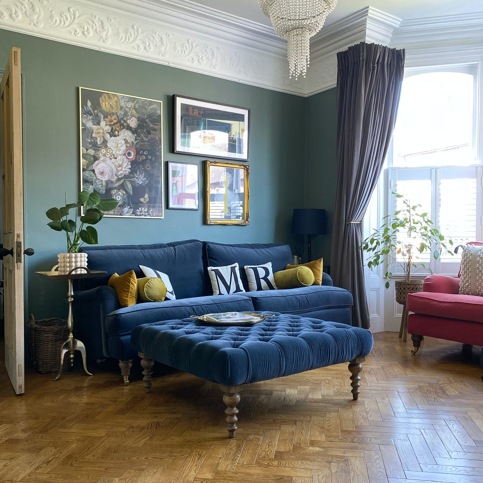 Living room with a sage green wall and a navy sofa