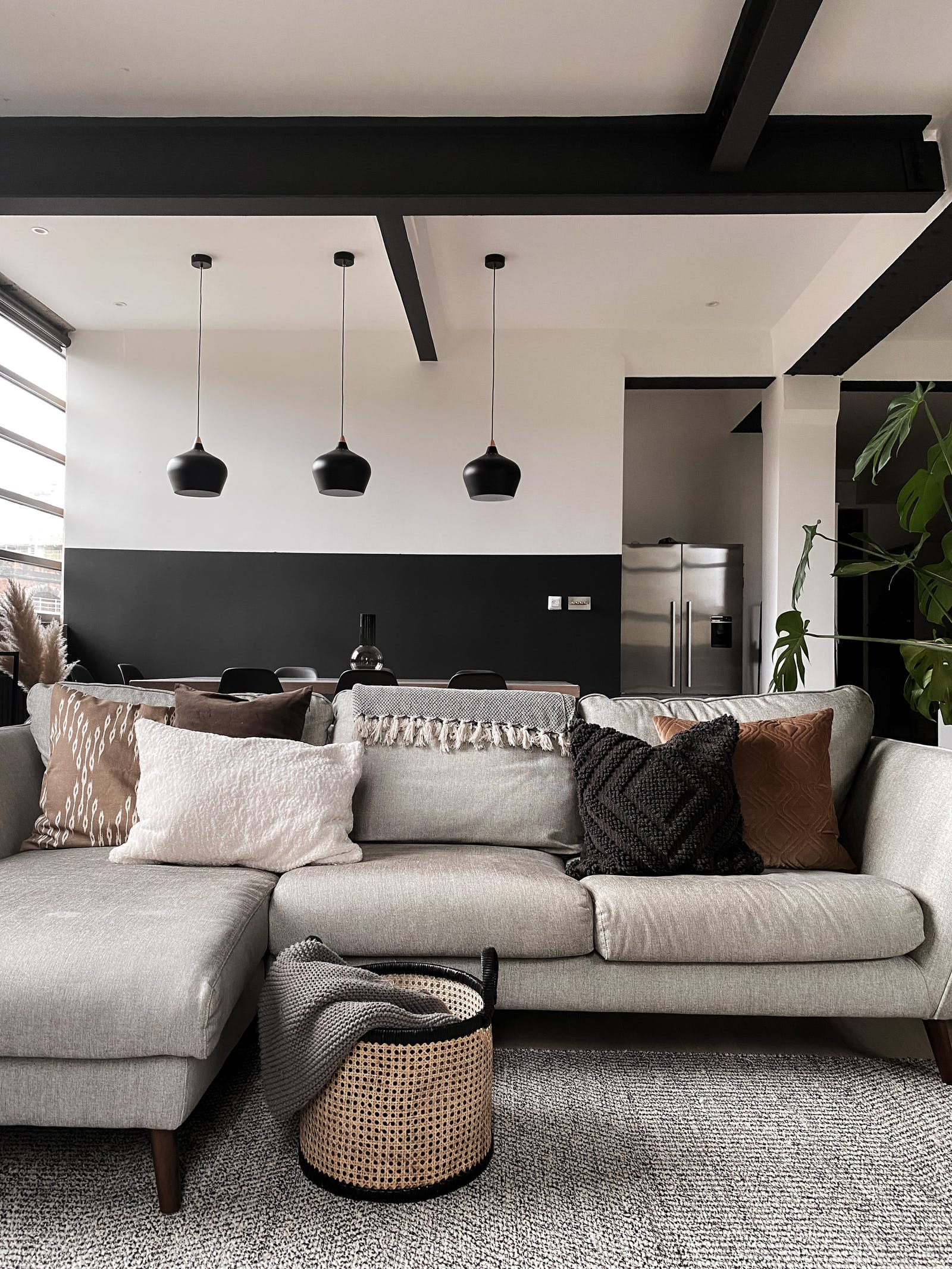 Living room with a grey sofa and an open plan dining area behind it