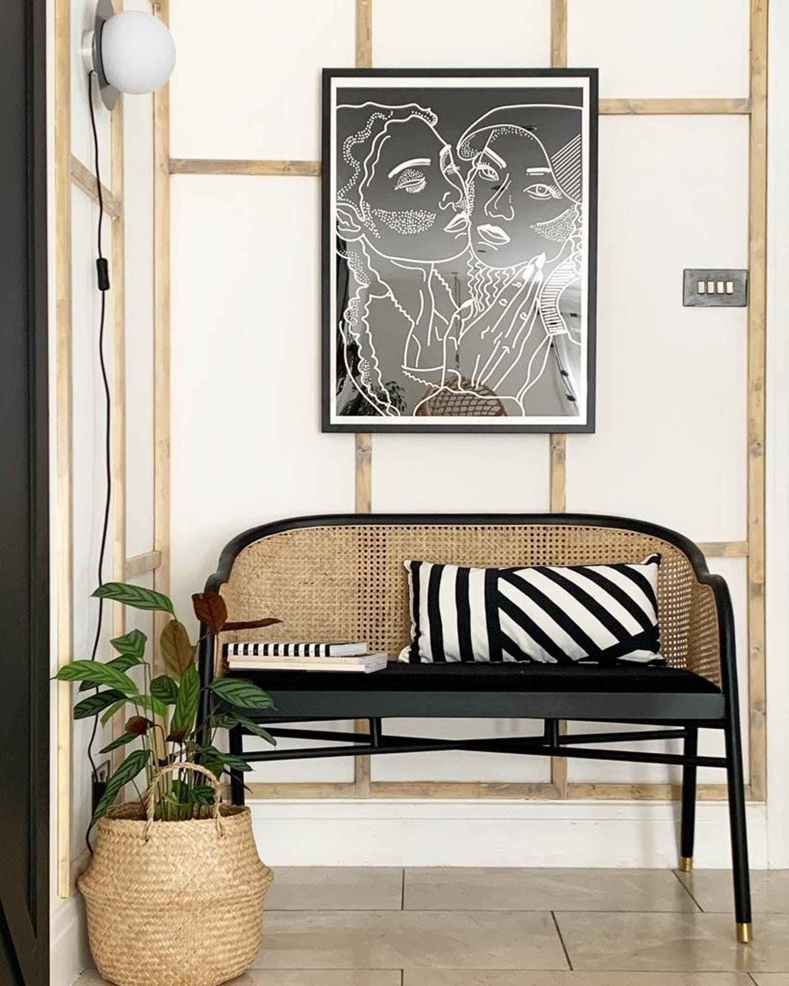 Rattan chair against a white and wooden panelling wall with a black and white patterned cushion on top