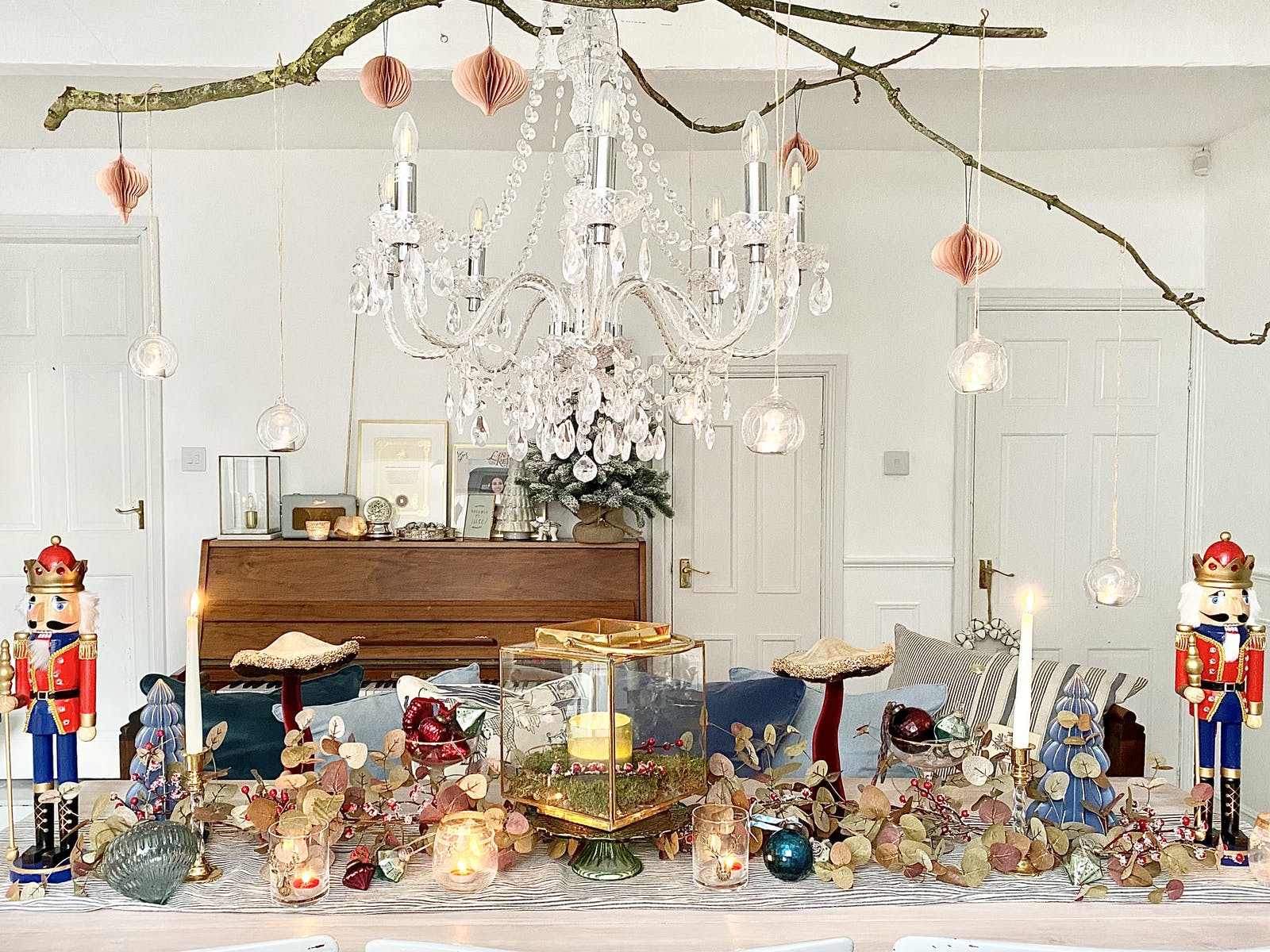 Dining table decked in Christmas decorations with large crystal chandelier