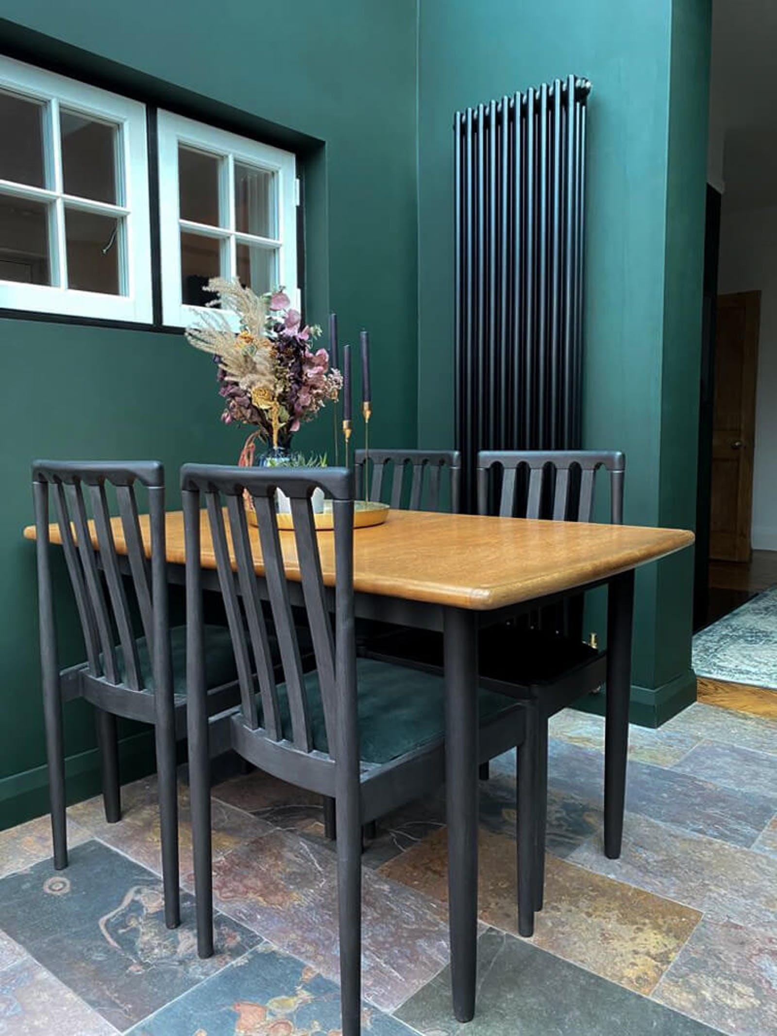 Dining room with dark green walls and dried flowers on the table