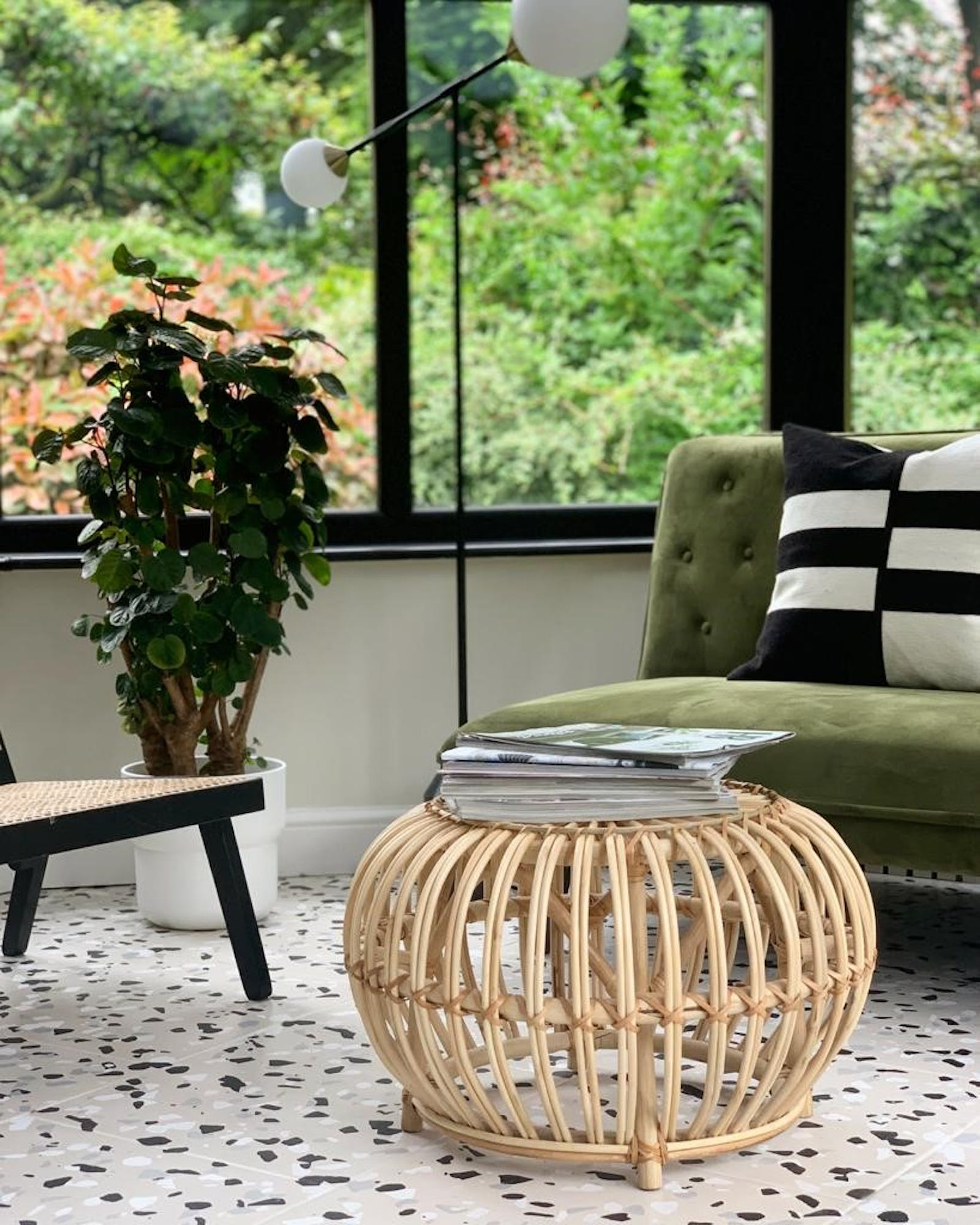 Green velvet sofa with a wooden rattan coffee table dressed in a stack of magazines