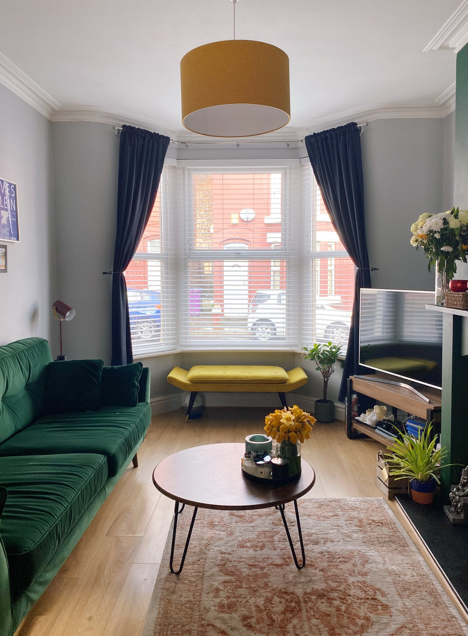 Bright living room with an emerald green sofa