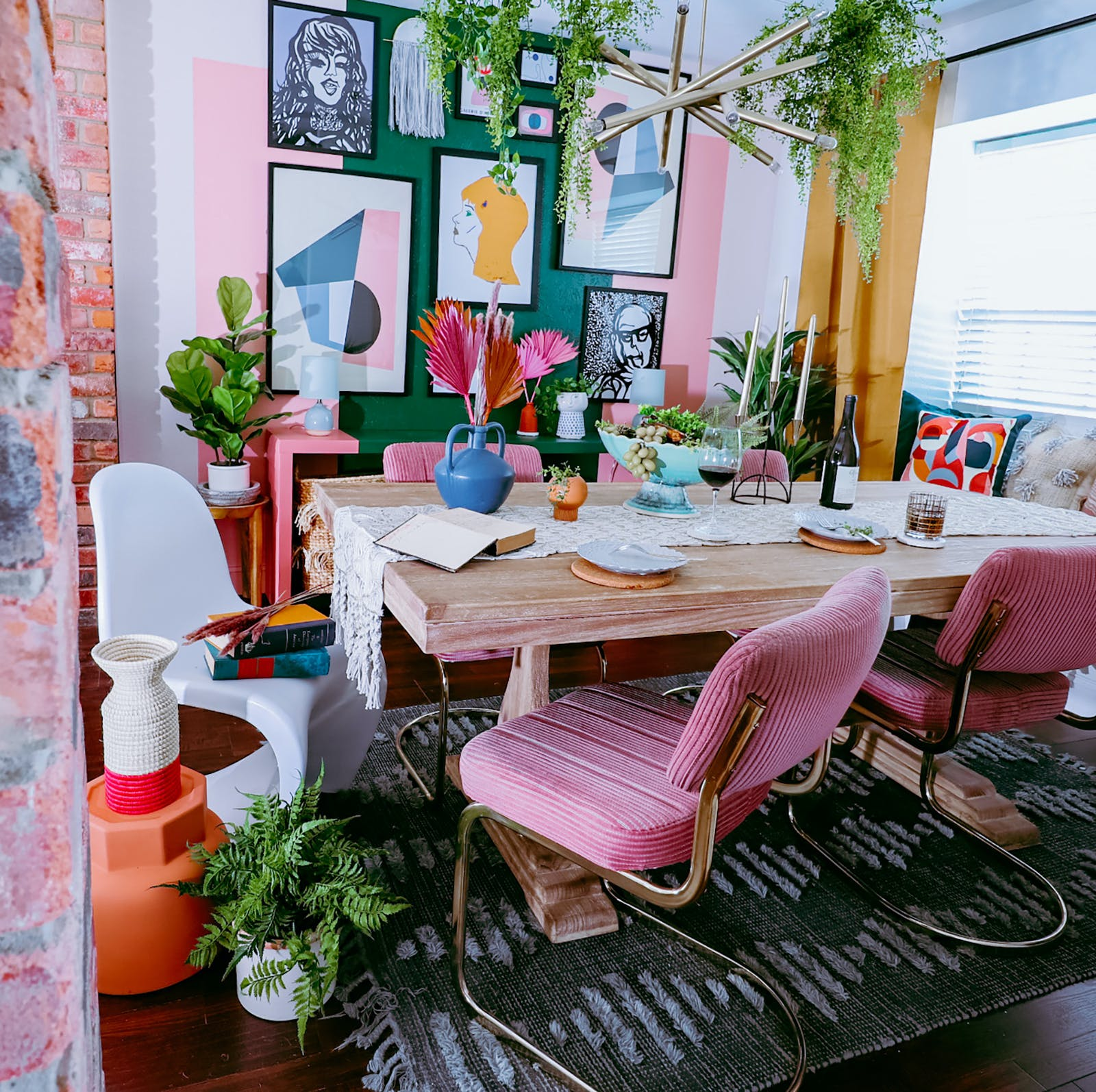 Image of dining table with pink chairs and a gallery wall