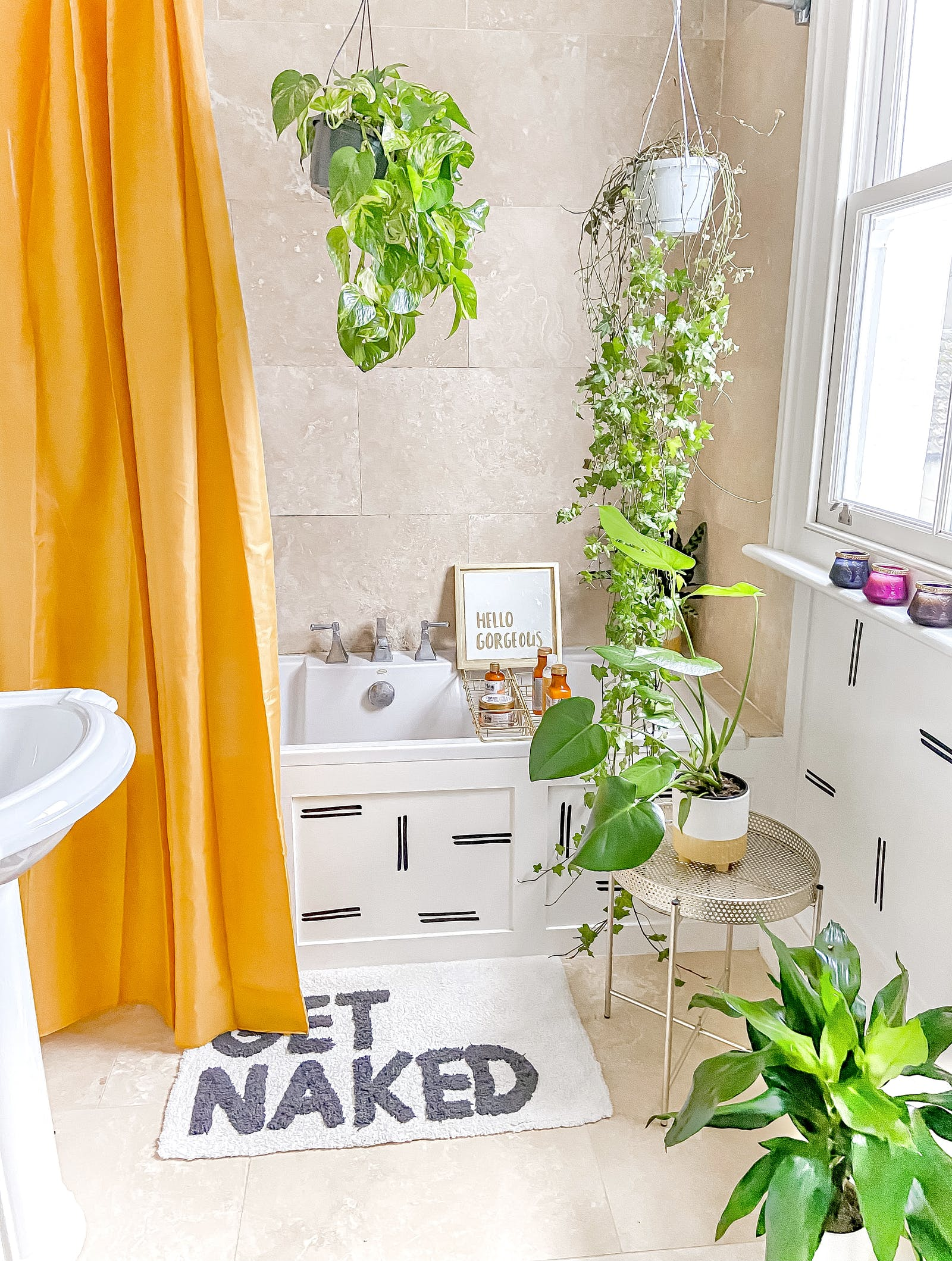 Brightly coloured bathroom with bright orange shower curtain and hanging plants