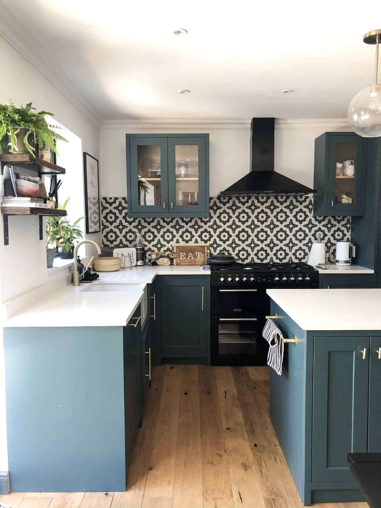 Kitchen with cabinets painted in teal and patterned black and white tiles behind the stove