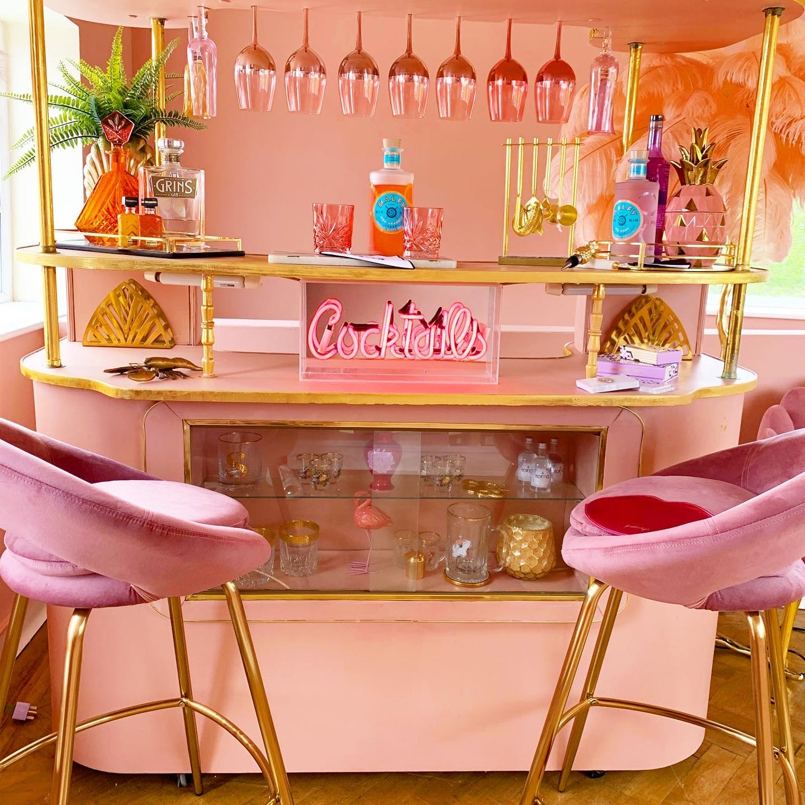 Retro-inspired cocktail bar in pink with plush chairs