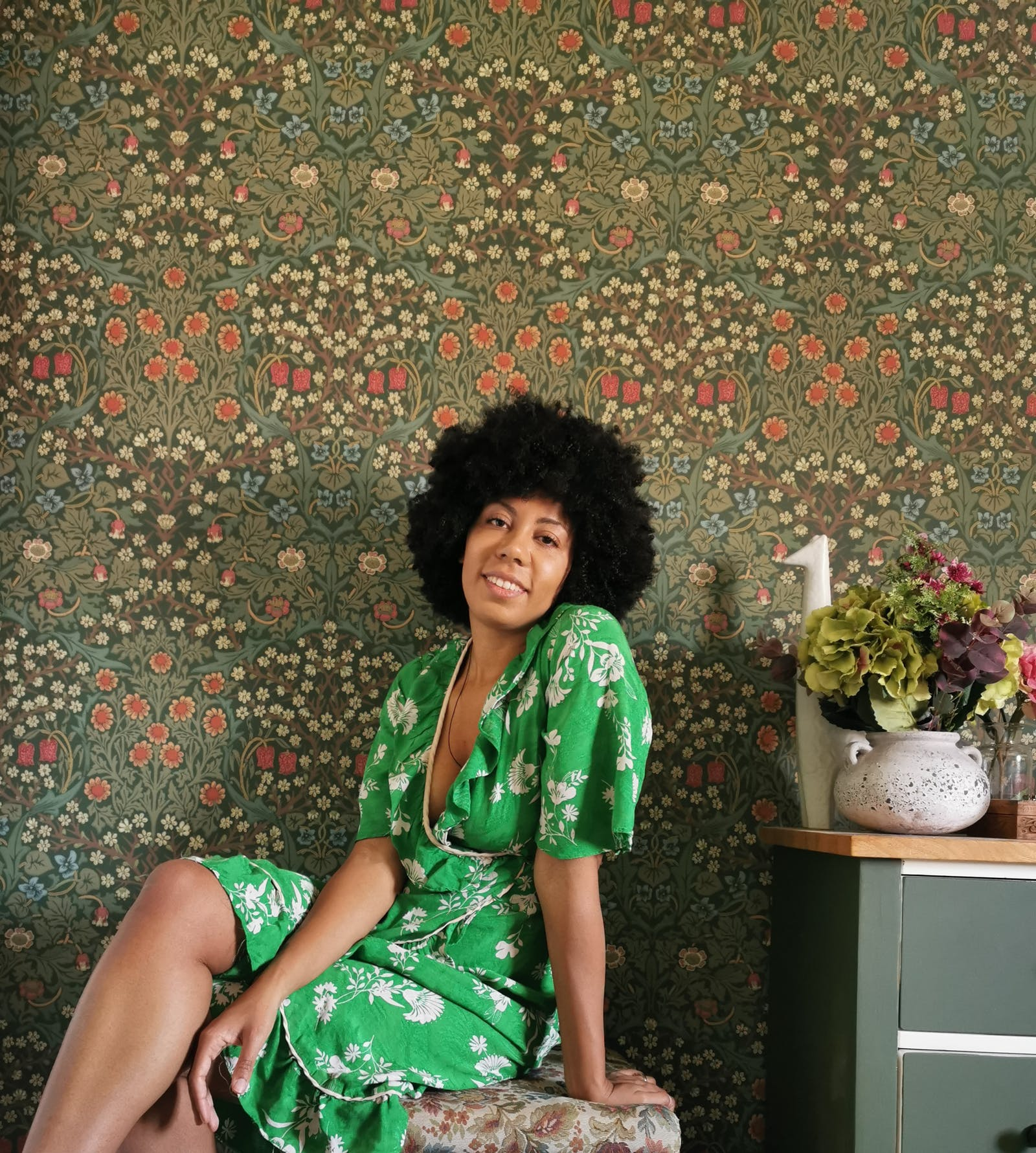 Woman in a floral green dress sitting in front of a grass green floral patterned wallpaper
