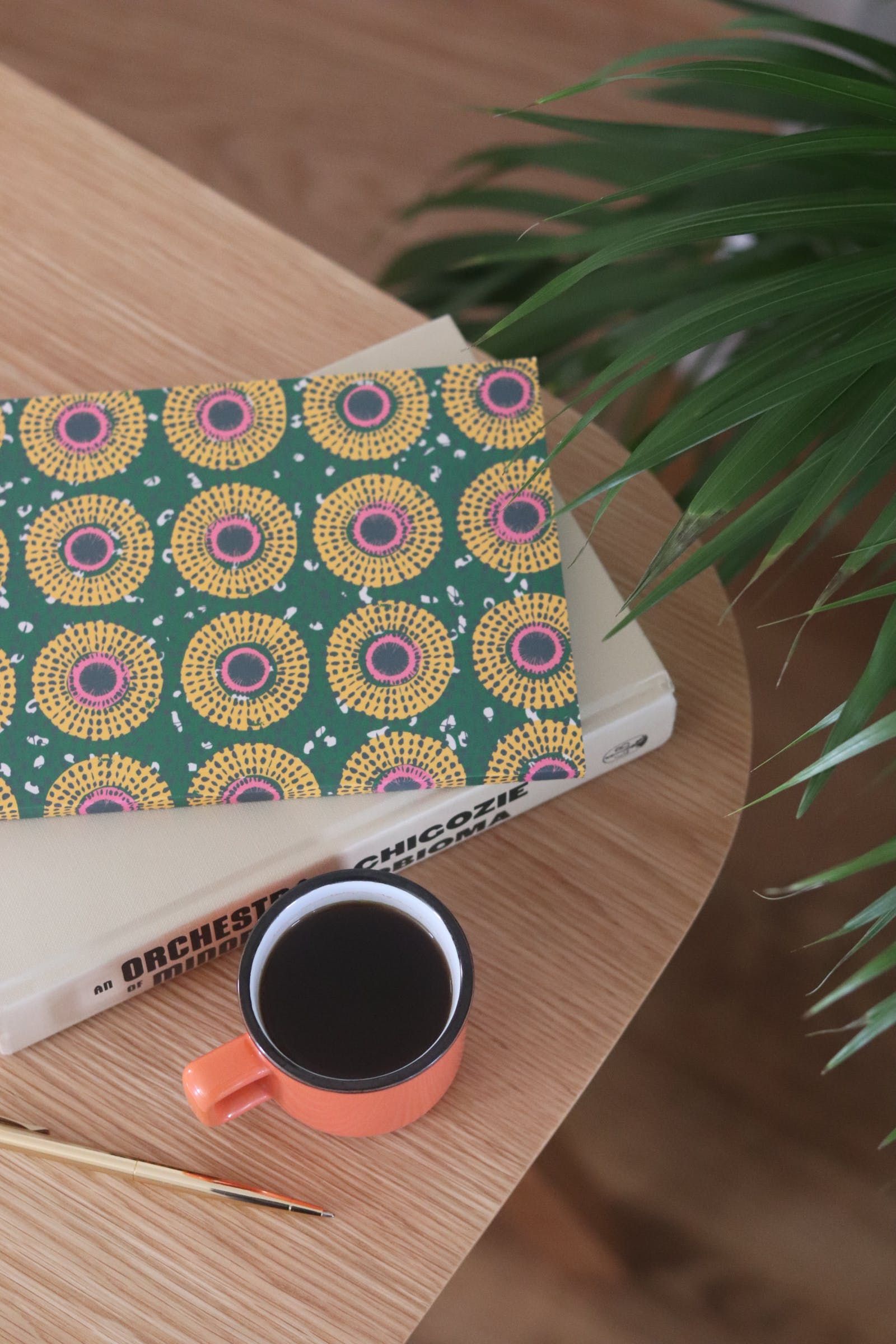 African print notebook next to a cup of coffee