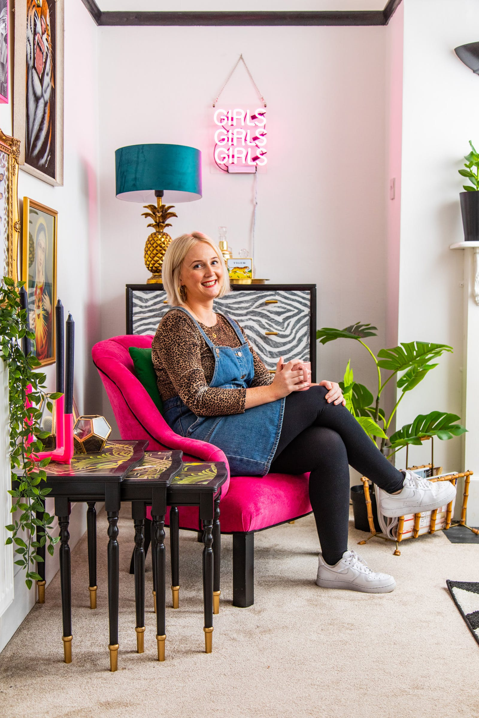 Blonde woman sitting on pink armchair in living room