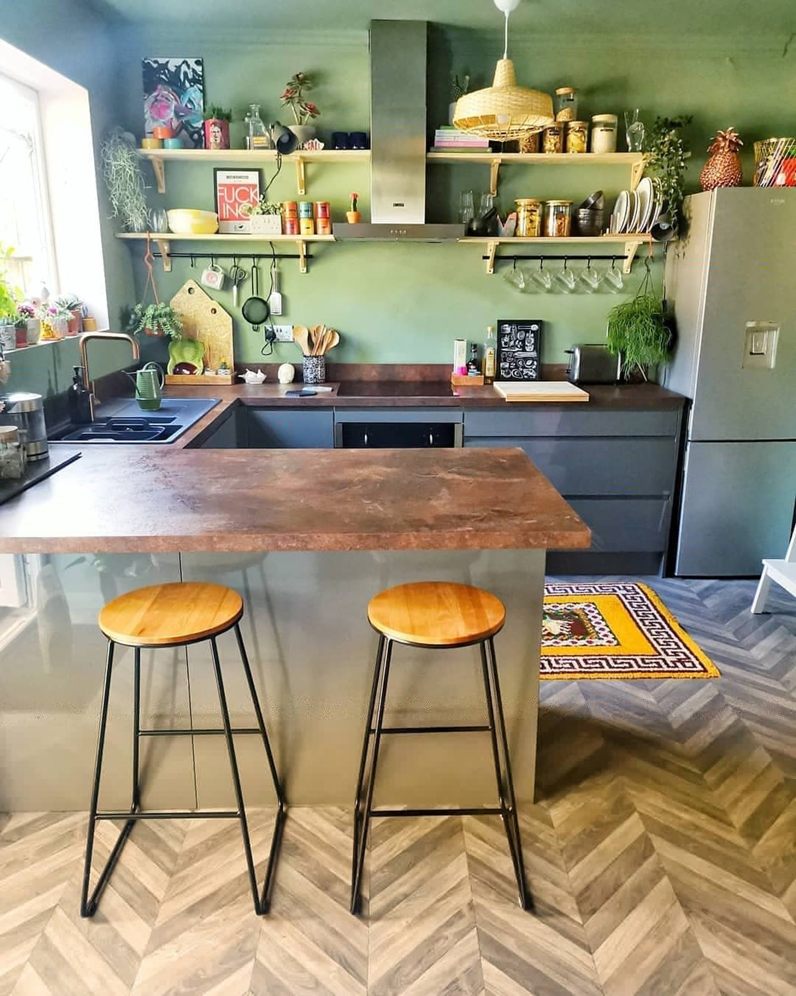 Kitchen painted in light green with wooden and vintage details