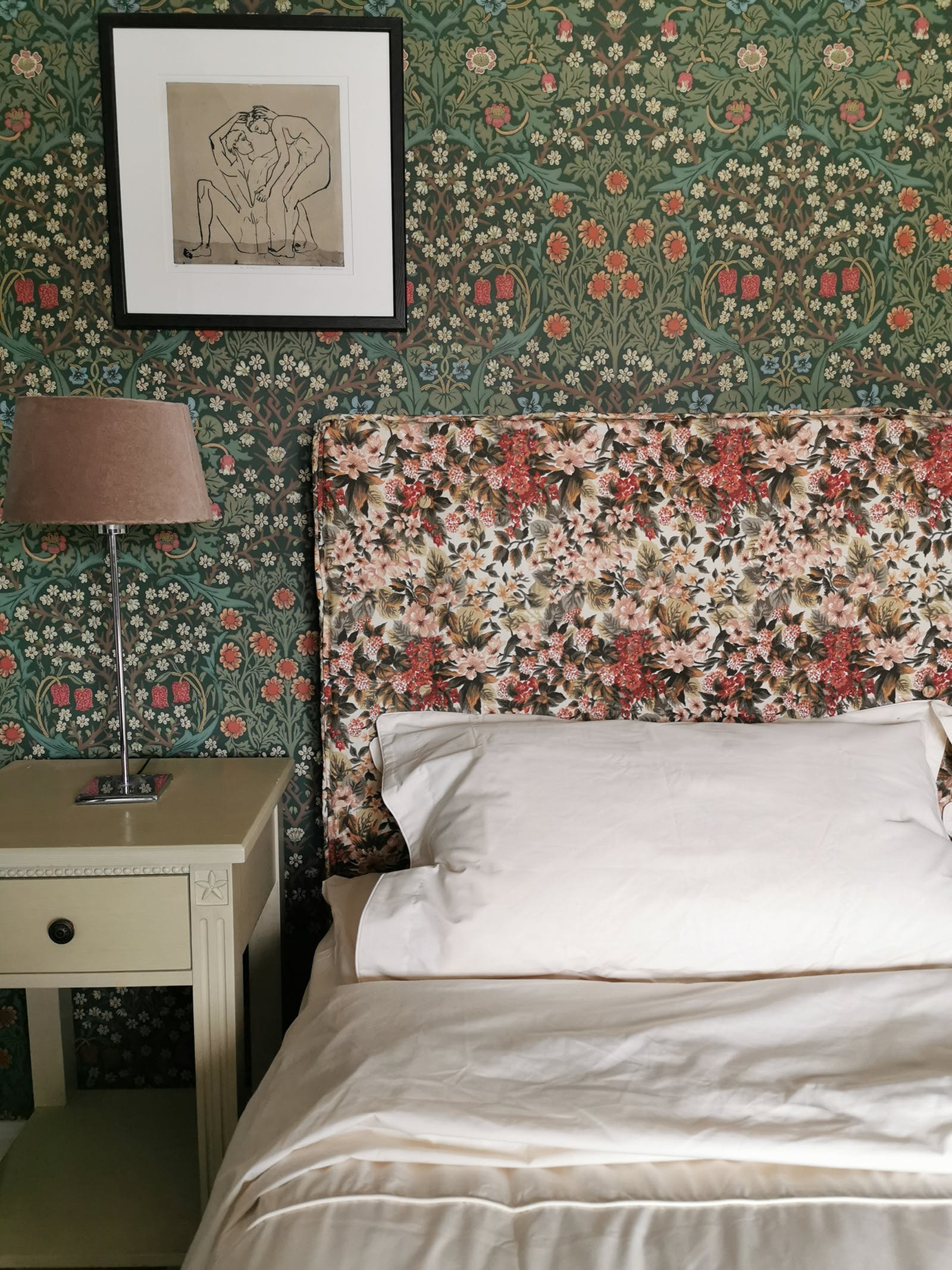 bedroom with a floral headboard and a floral patterned wallpaper with artwork