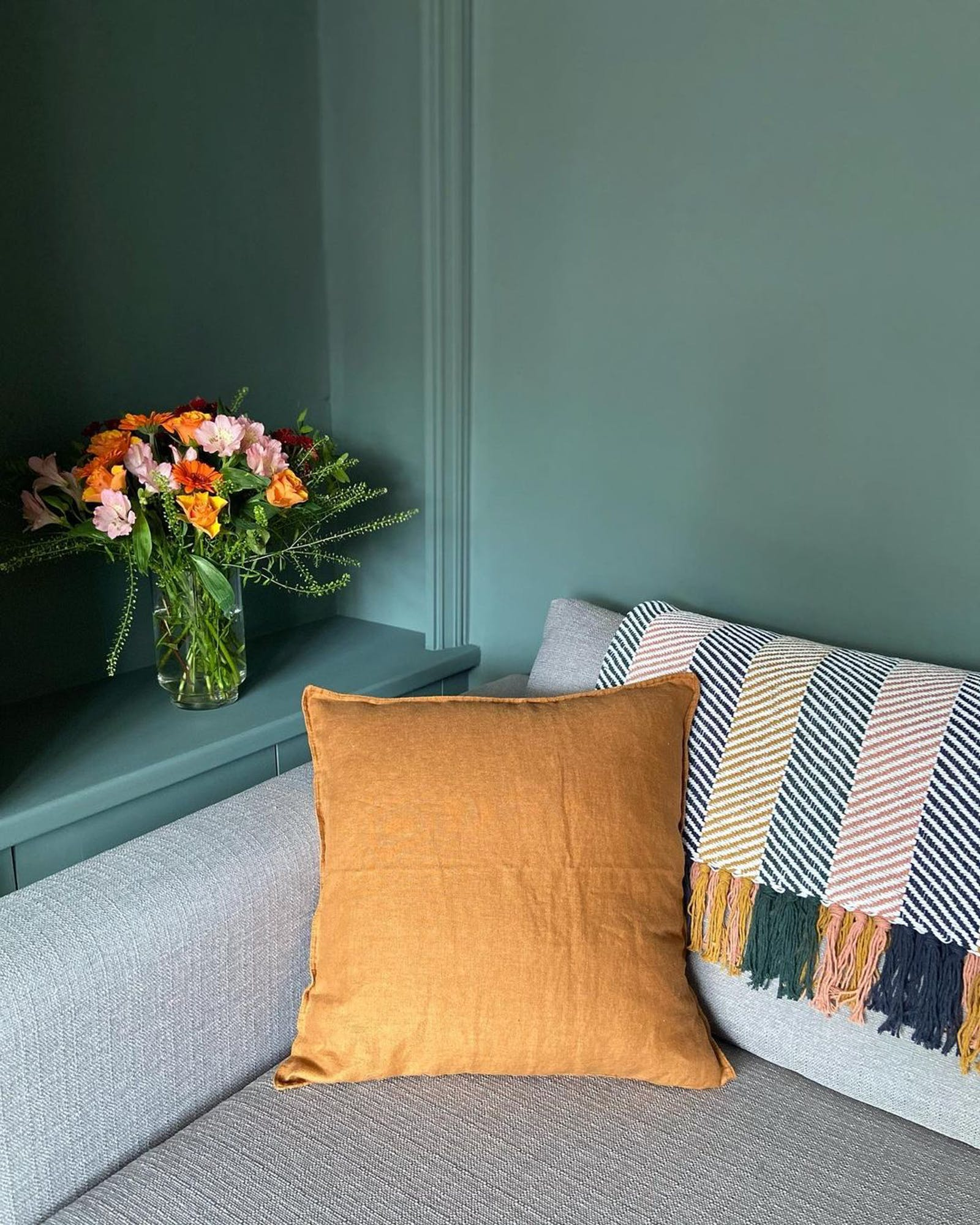 Living room painted in Lick Green 03 painted walls with bright yellow cushion and flowers in a vase