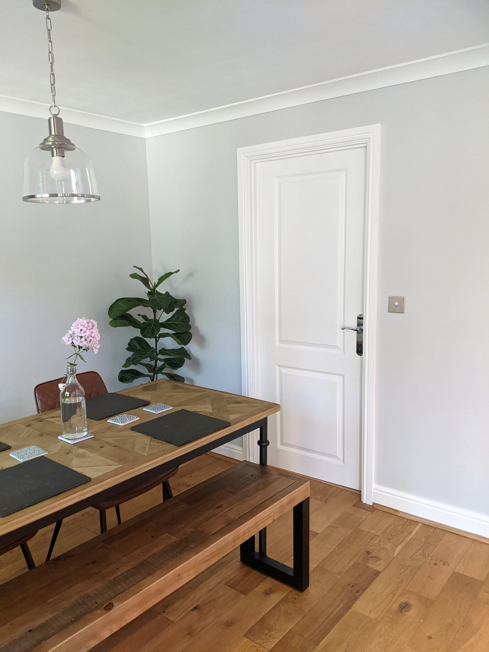 Dining room painted in Lick Grey 02, with a bench-style dining table and light pink flowers for decoration