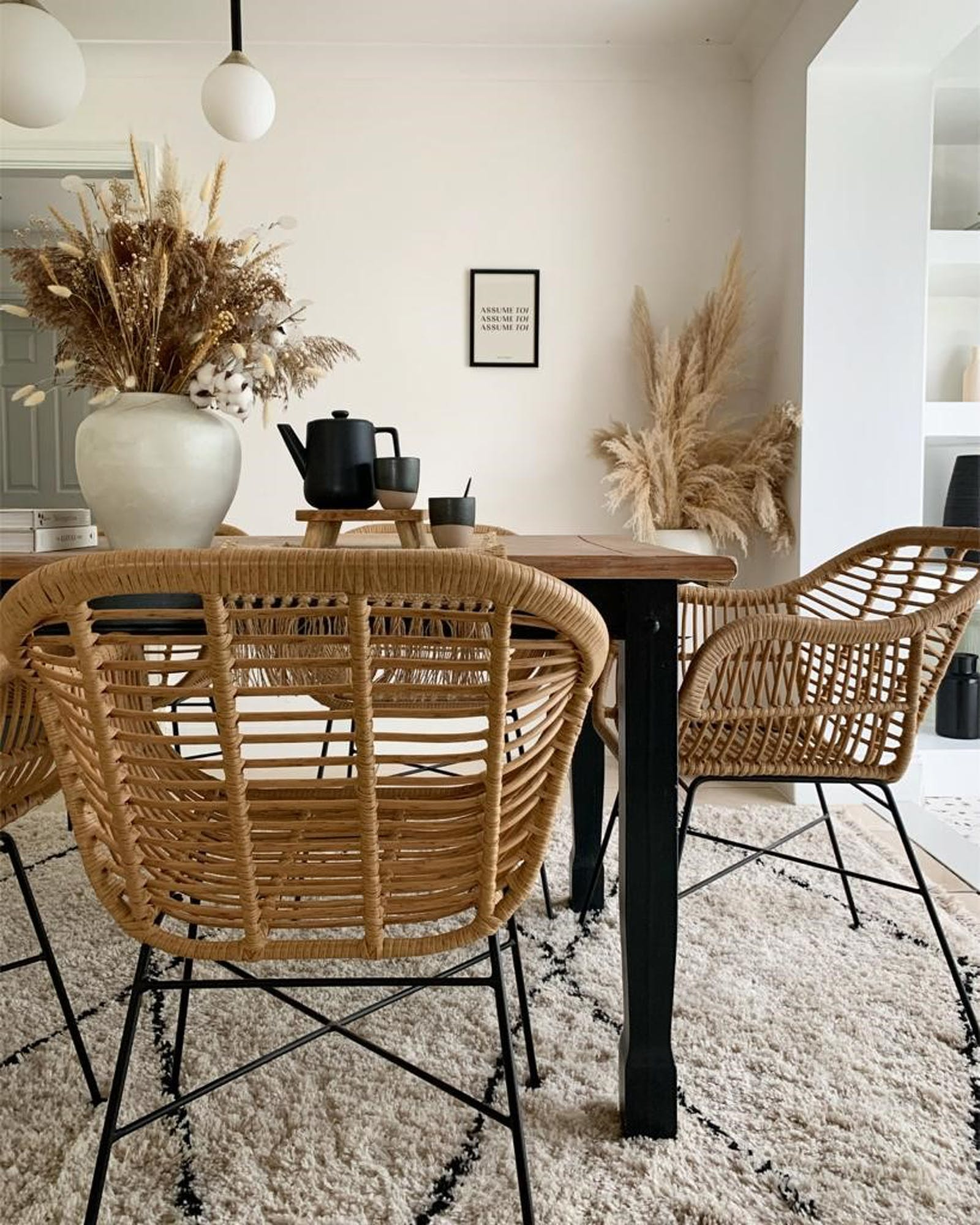 Wooden dining table with rattan chairs and dried foliage in vases
