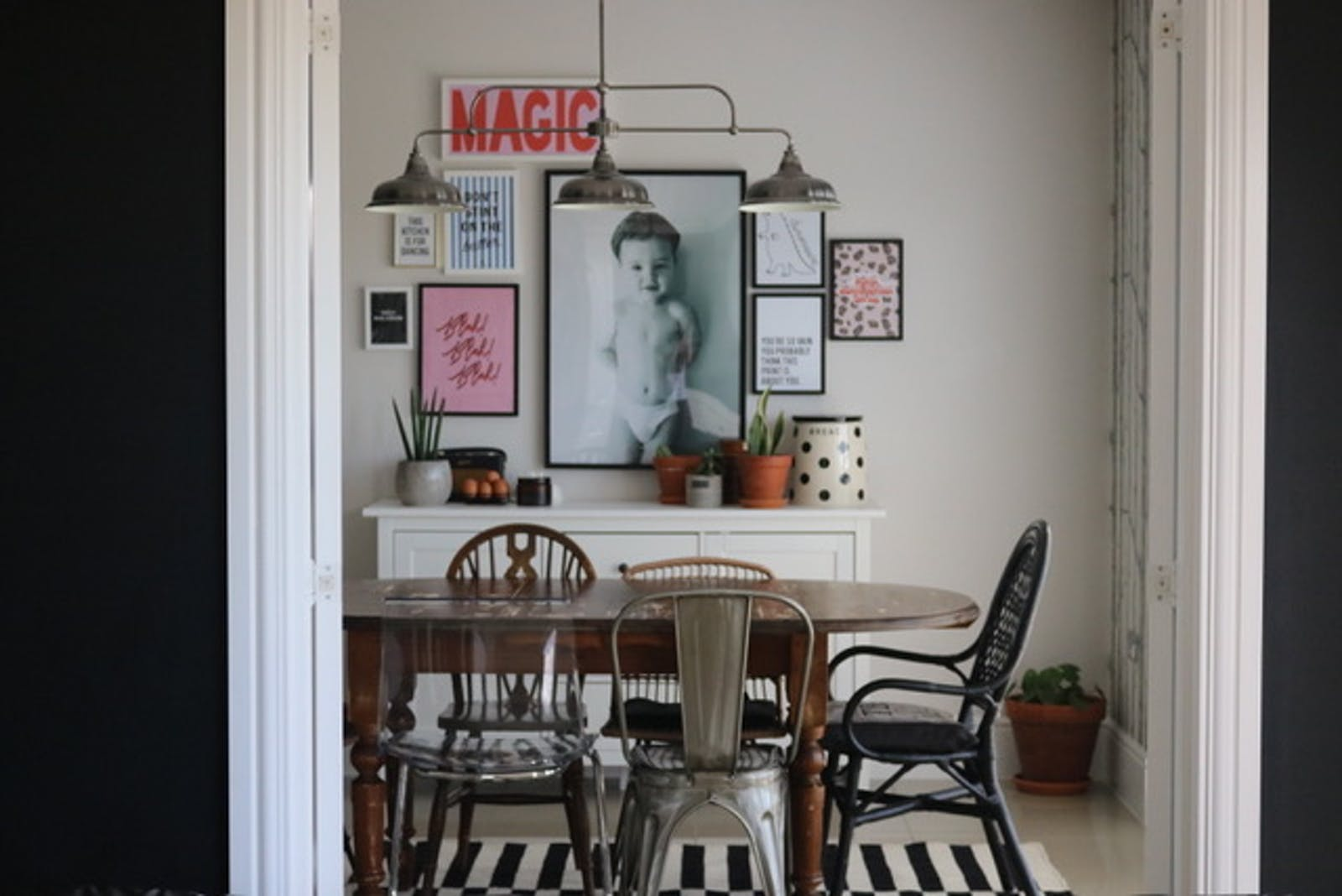 Dining table with photos and posters placed on the wall behind it
