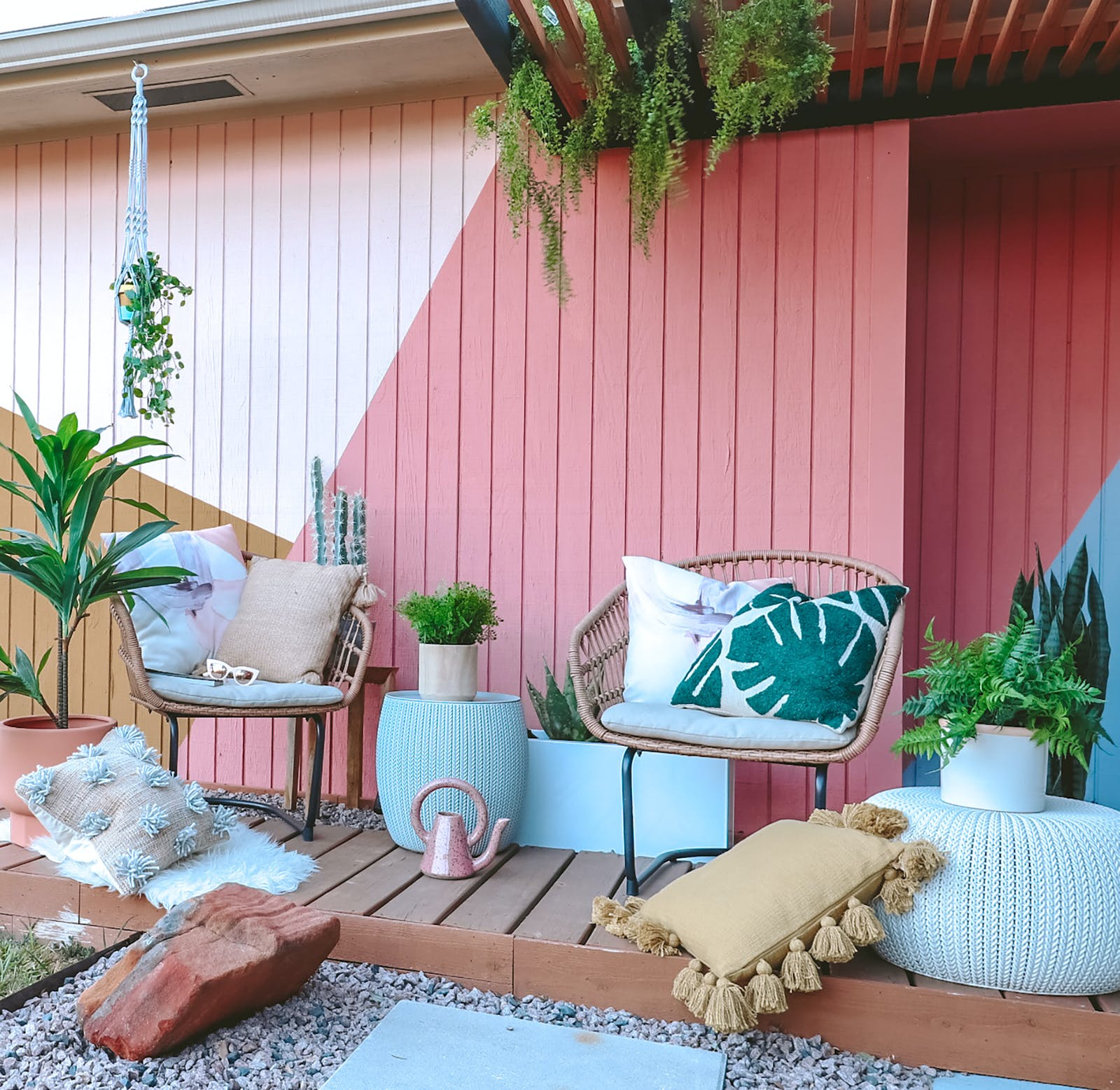 Image of a bohemian inspired backyard with wooden panelling and large cushions
