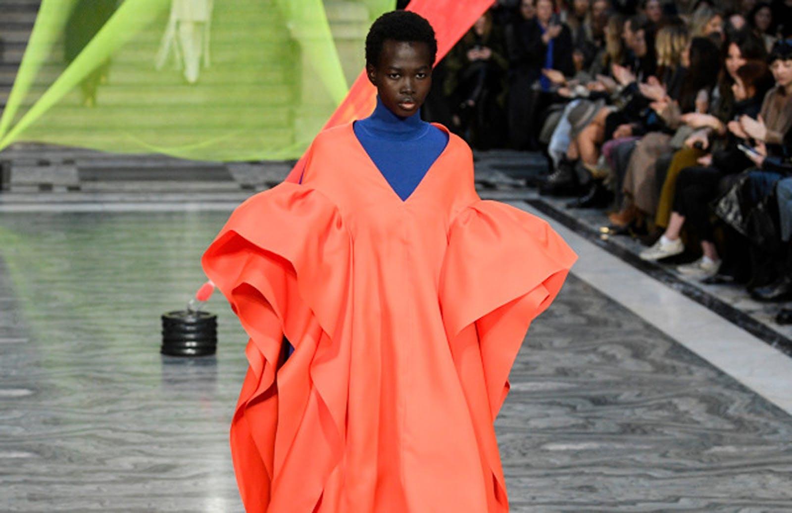 Fashion week shot of woman wearing bright orange dress