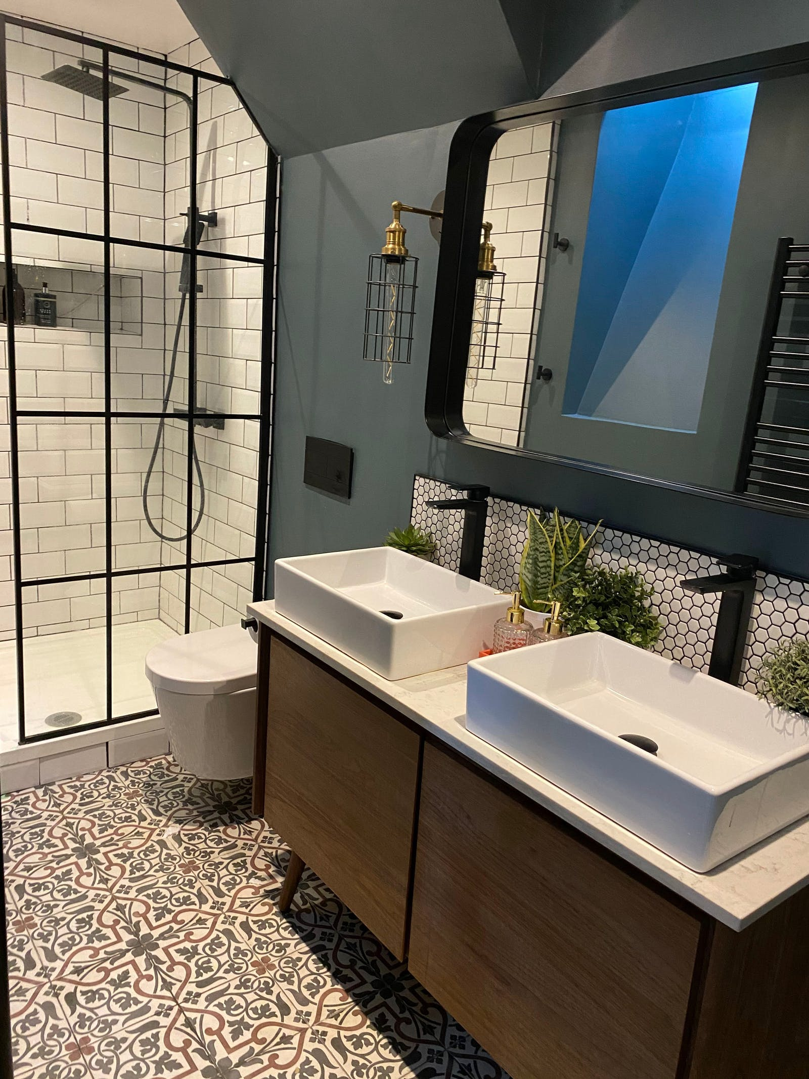 Dark blue bathroom with an assortment of tiles and double sinks