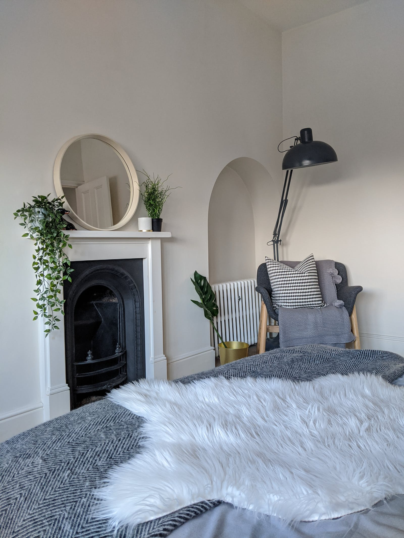Bedroom with white walls and a fireplace