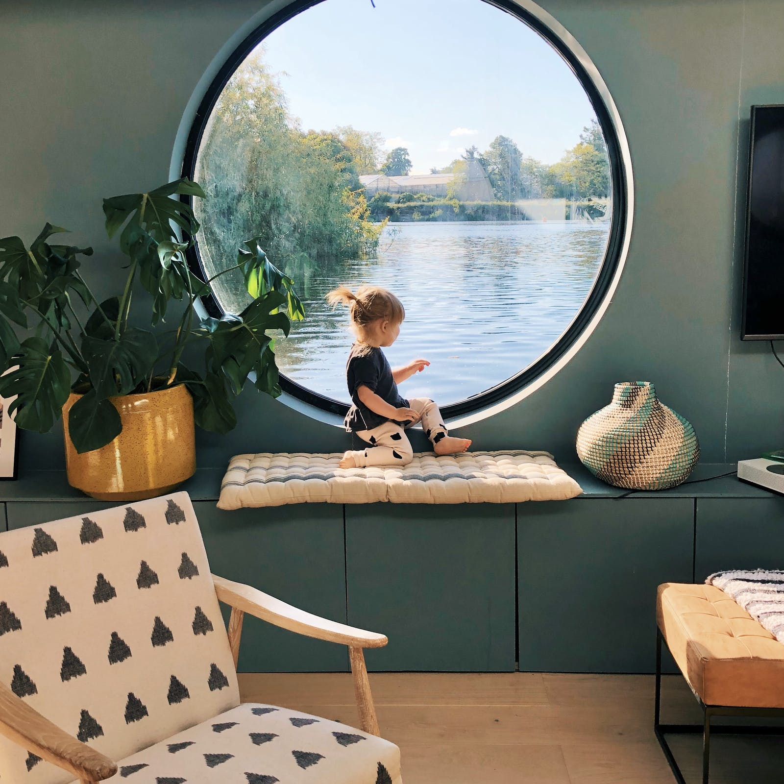 Child sitting in front of a large circular window in a teal painted living room