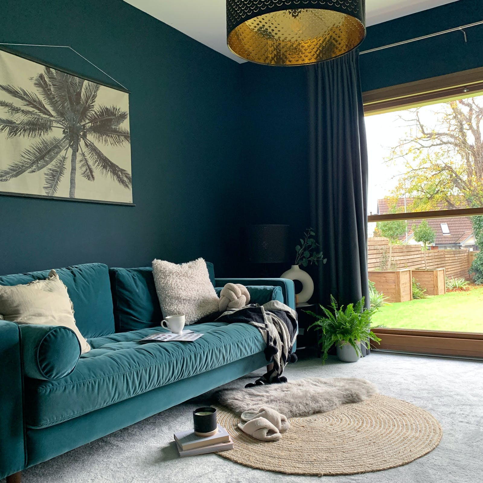 Dark blue lounge area, with a teal sofa and palm tree print on the wall