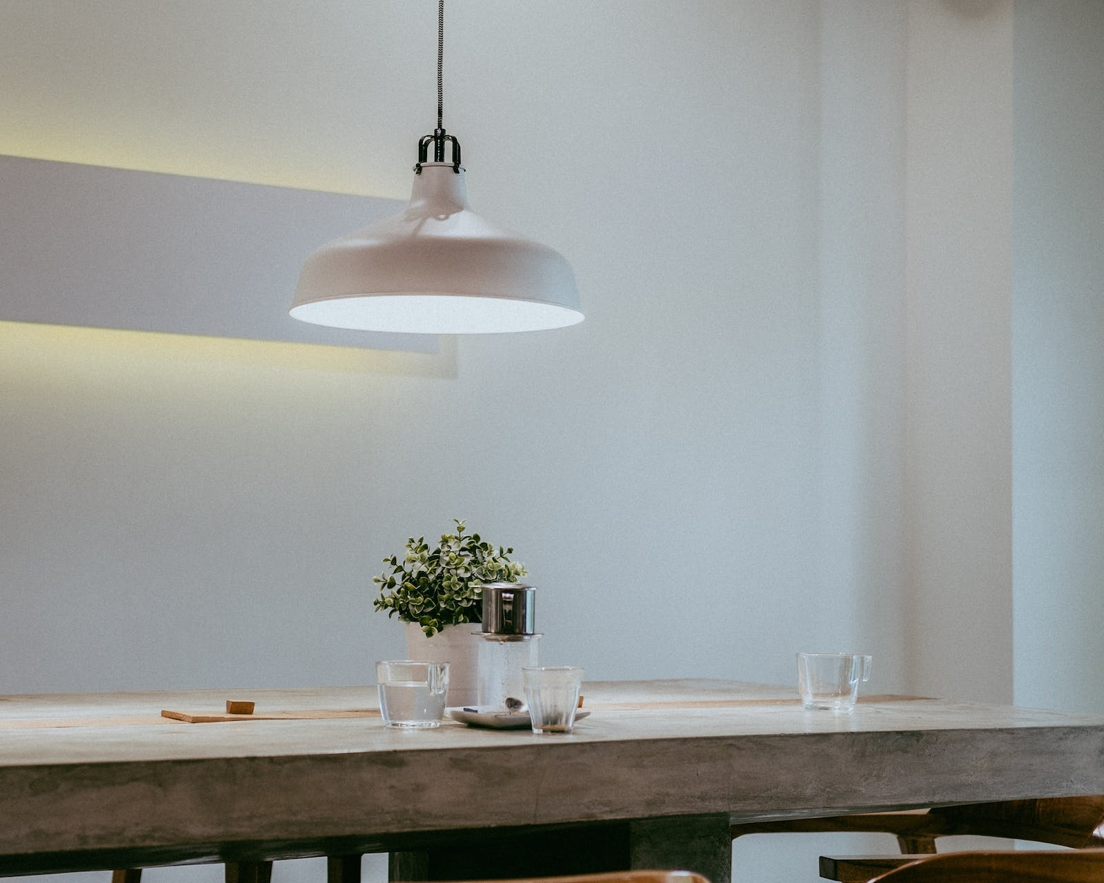White dining room with solid wood dining table in minimalistic setting