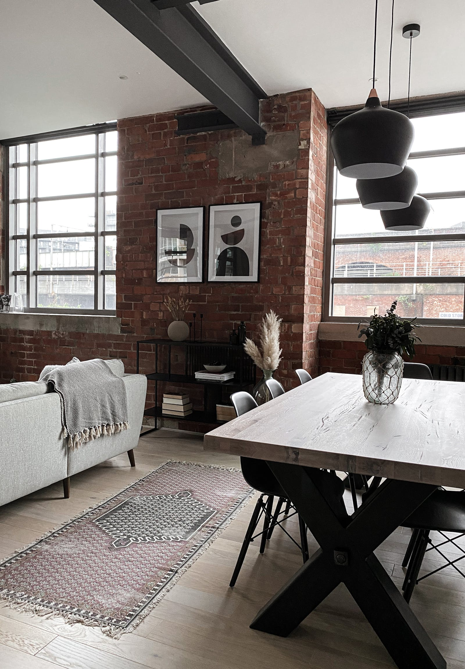 Open space living and dining room with an exposed brick wall