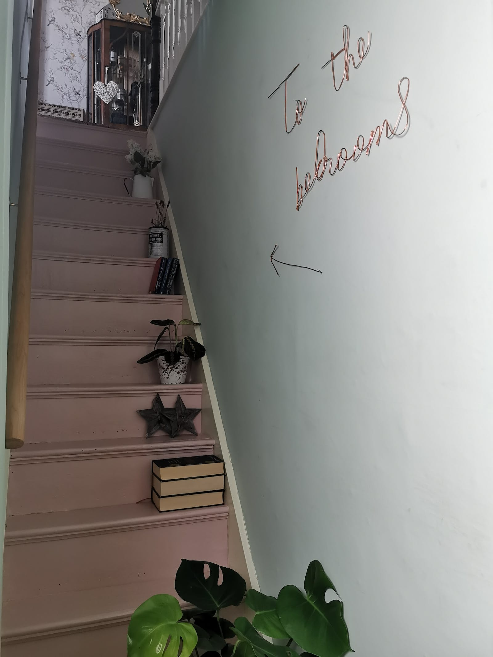 Narrow stairs painted in pink with a neon sign on the wall that says 'To the bedrooms'