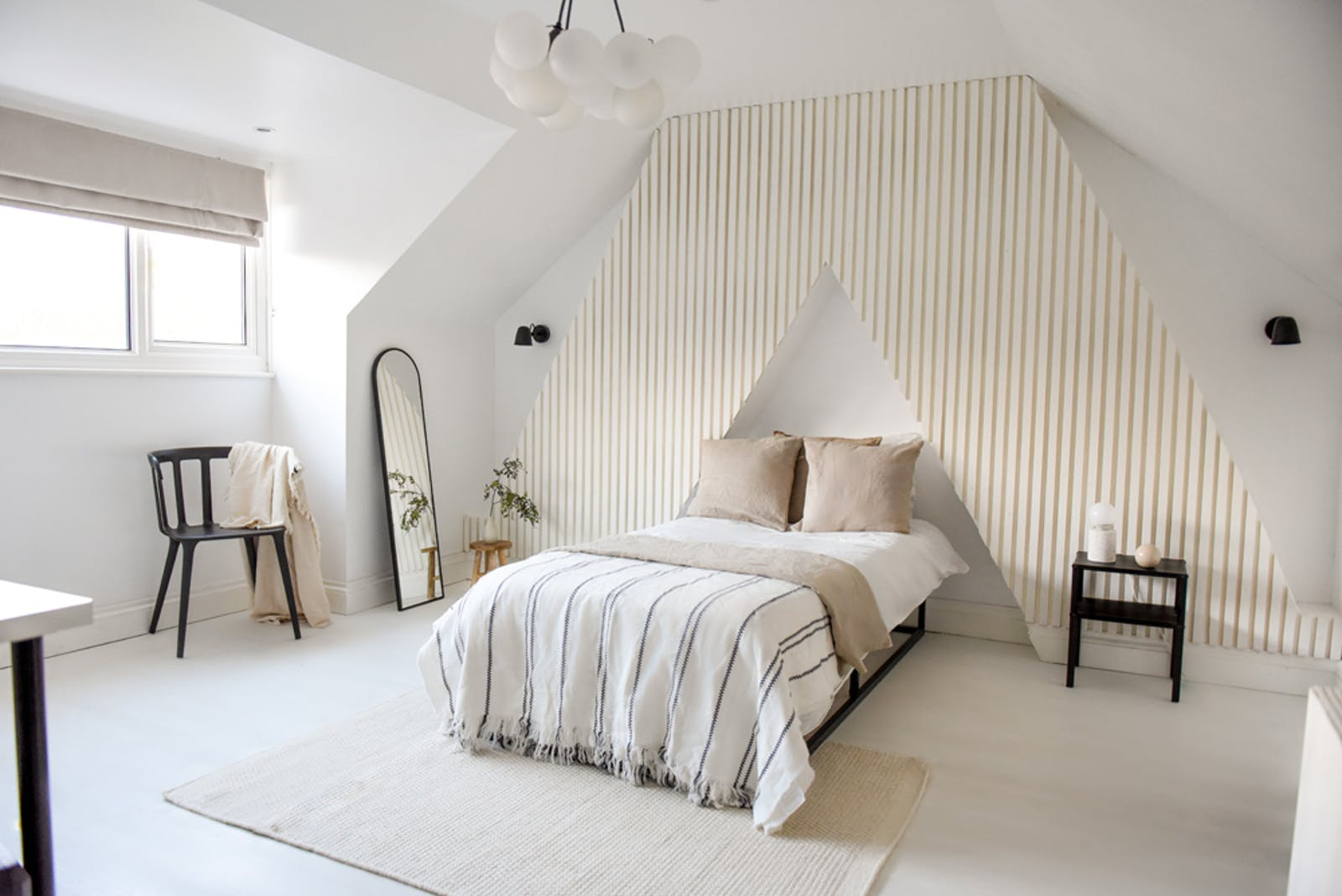 Loft bedroom with Lick White 03 wall panelling behind the bed