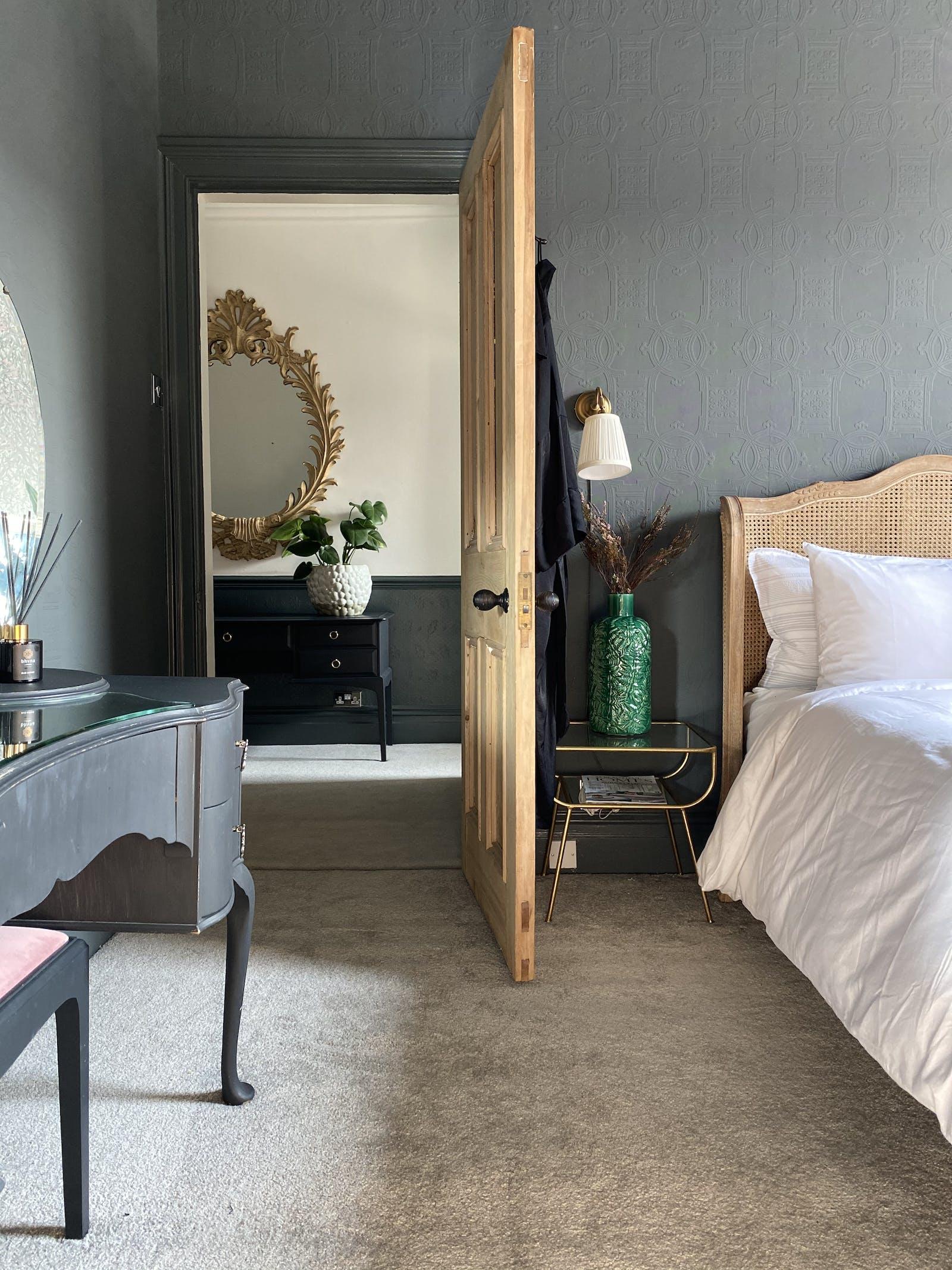 Open wooden door leading to a bedroom in medium grey colour