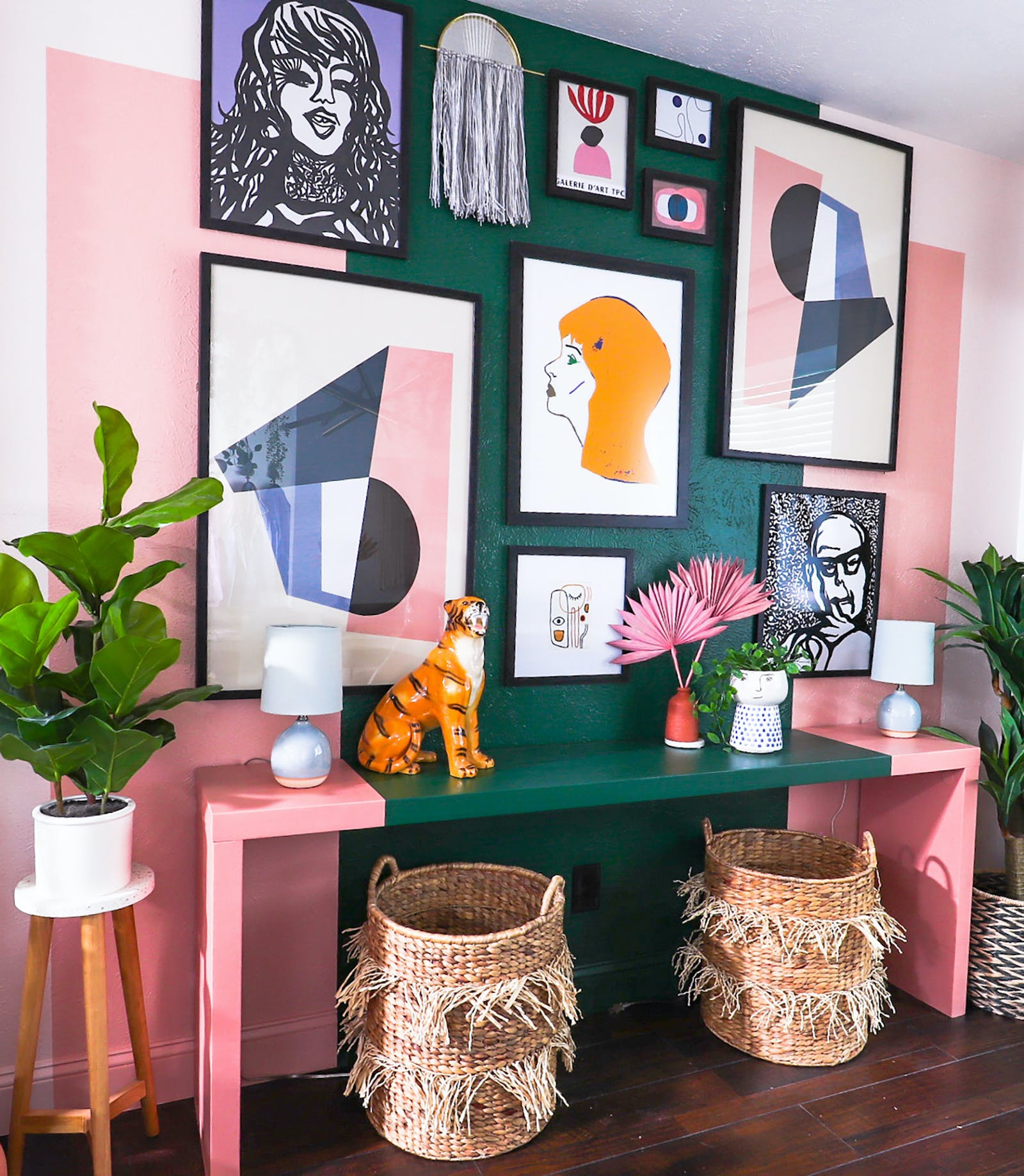 A gallery wall of art work in a vibrant hallway, painted green and pink in geometric shapes