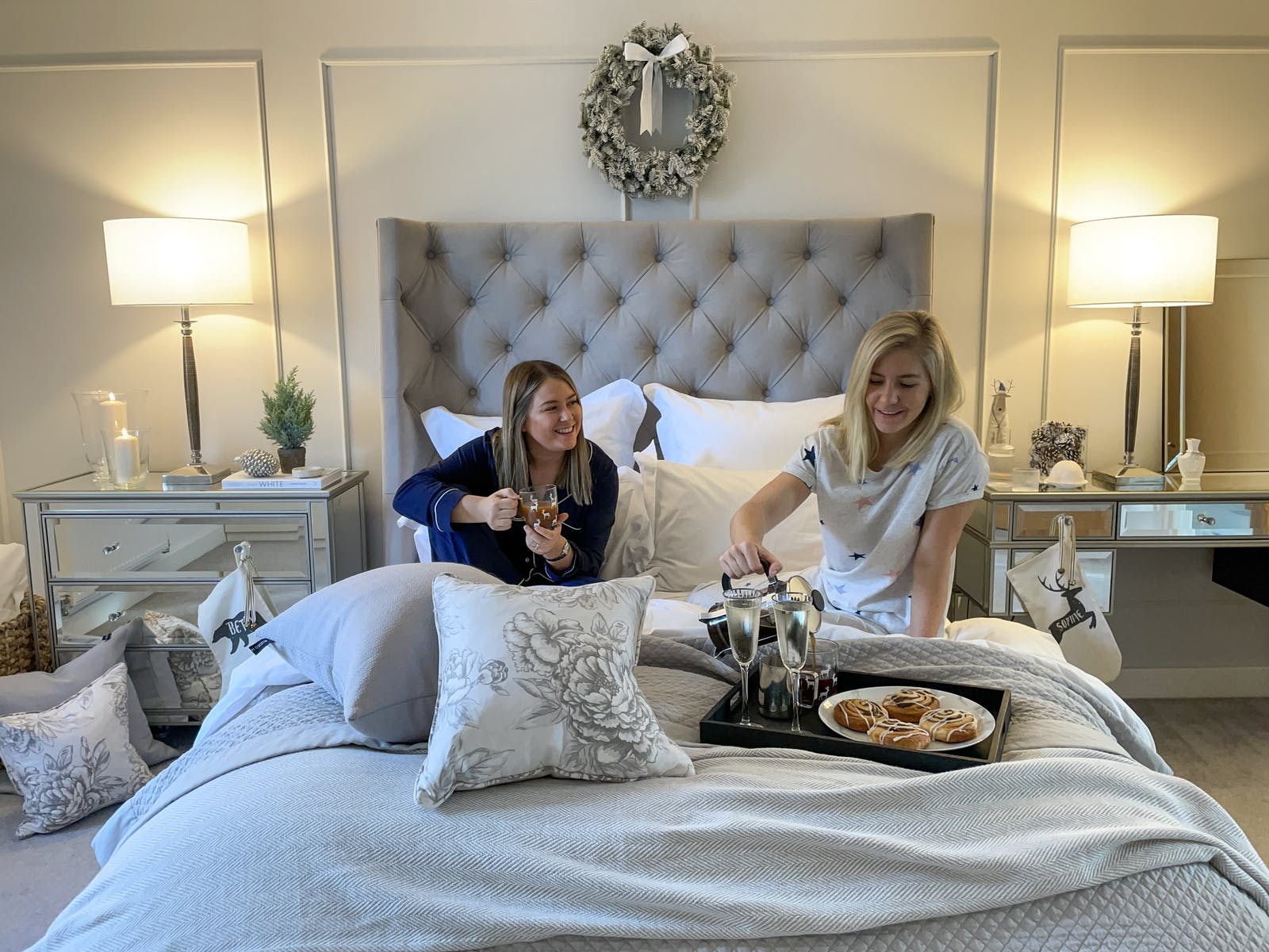 A blonde and brunette woman sitting on bed with breakfast pastries